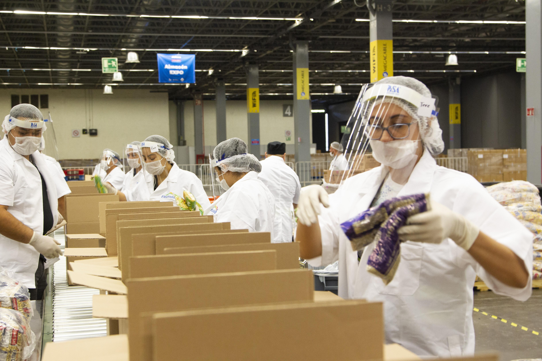 Personal de blanco con careta y guantes empacando despensas
