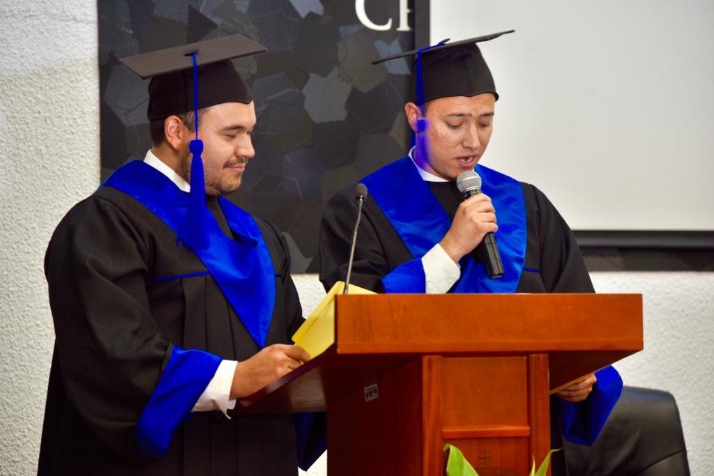 Representantes de generación en pódium dirigiendo mensaje graduados