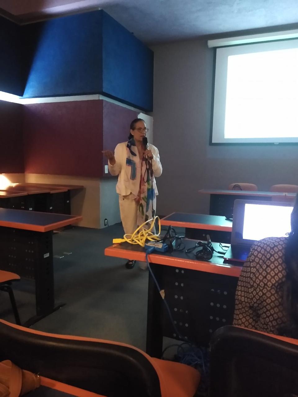 Conferencista al micrófono, detrás una diapositiva