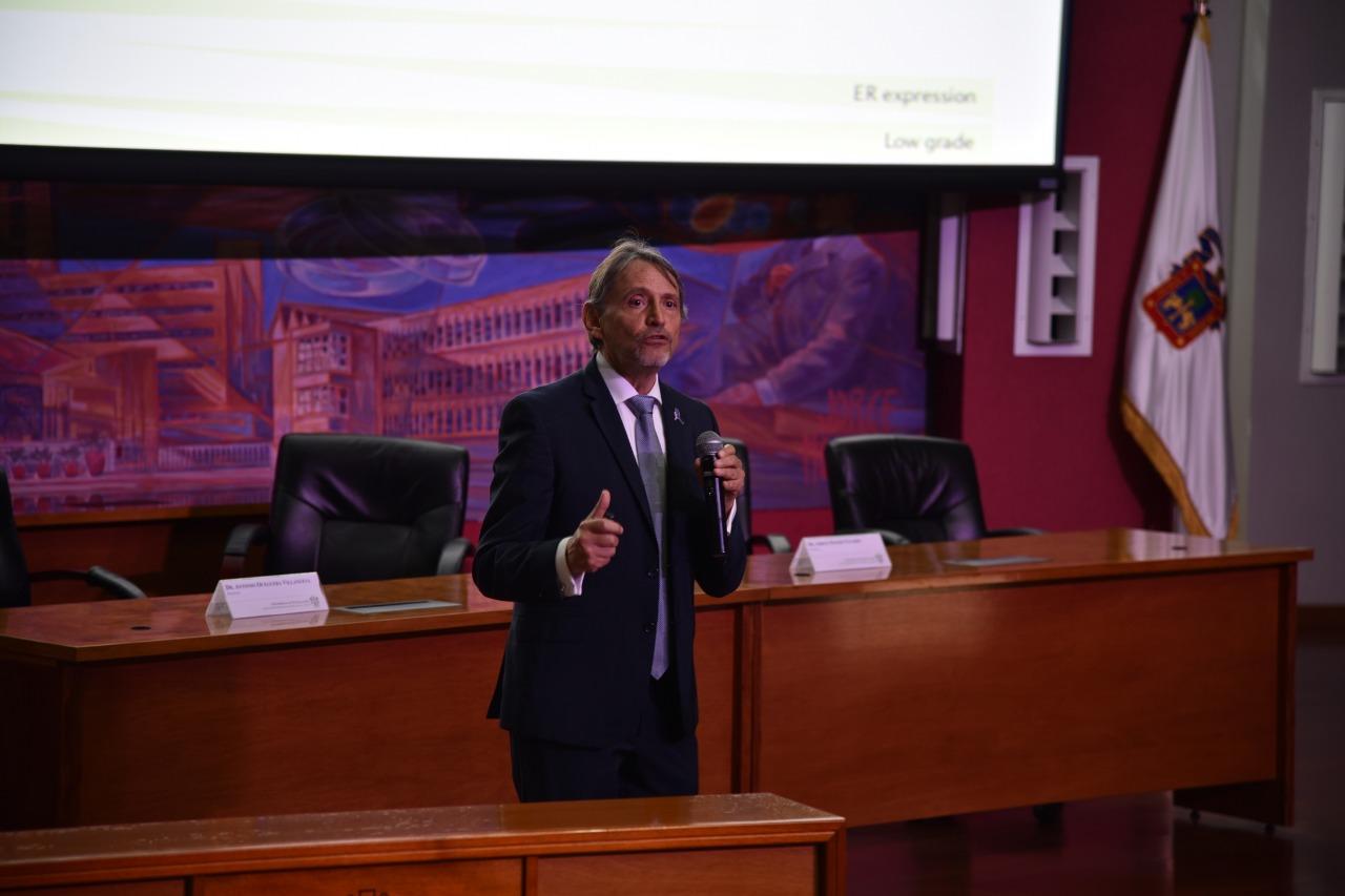 Ponente impartiendo conferencia al centro del auditorio y abajo del escenario