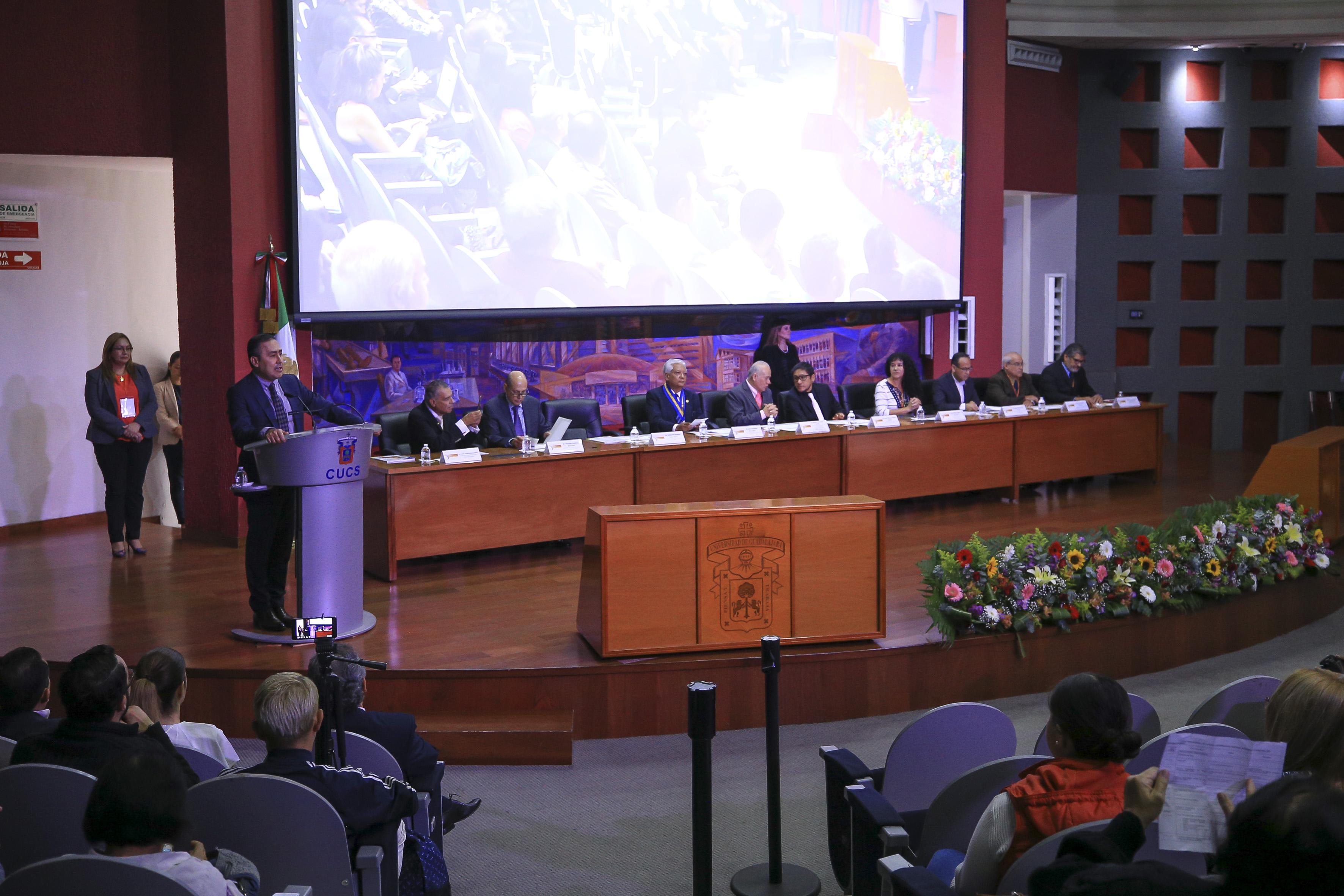 Rector CUCS en podio ofreciendo mensaje, toma amplia