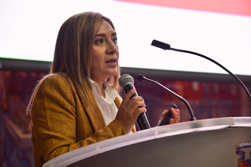 Tercera conferencista durante el conversatorio haciendo uso de la voz en pódium