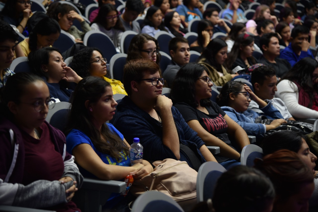 Alumnos atentos a la conferencia en auditorio lleno