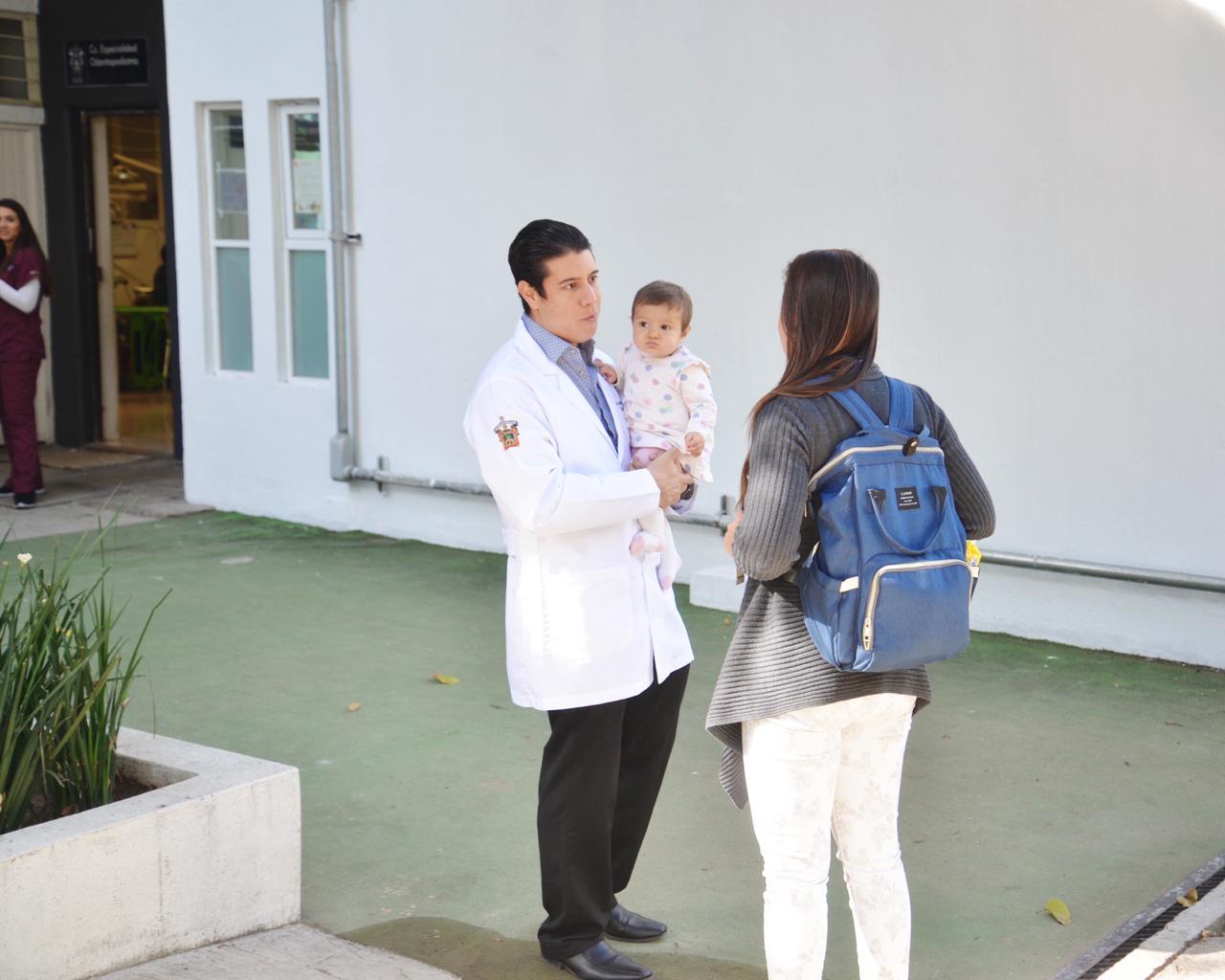 Coordinador Especialidad en Odontopediatría, cargando a una bebé y recibiendo a una mamá en la clínica