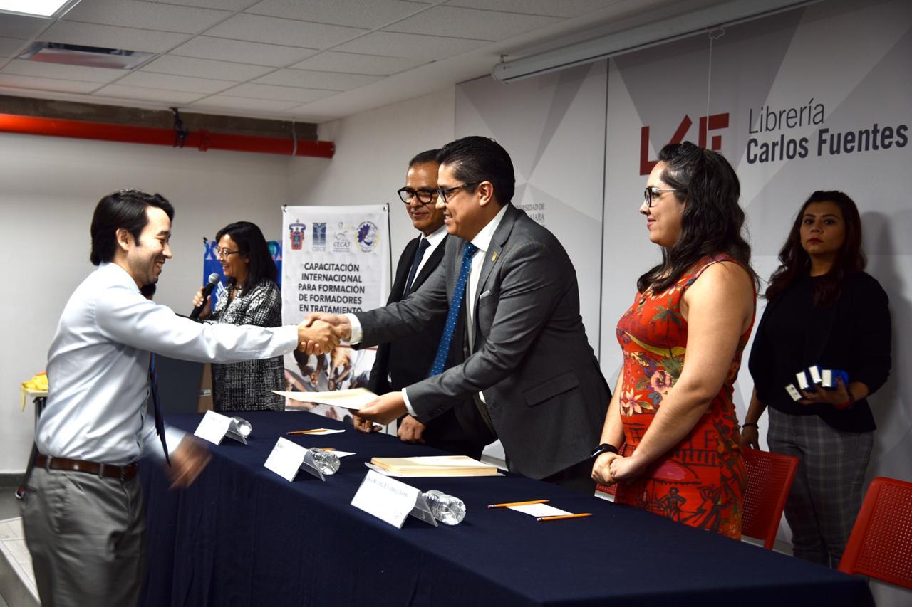 Rector del CUCS entregando reconocimiento a académico graduado