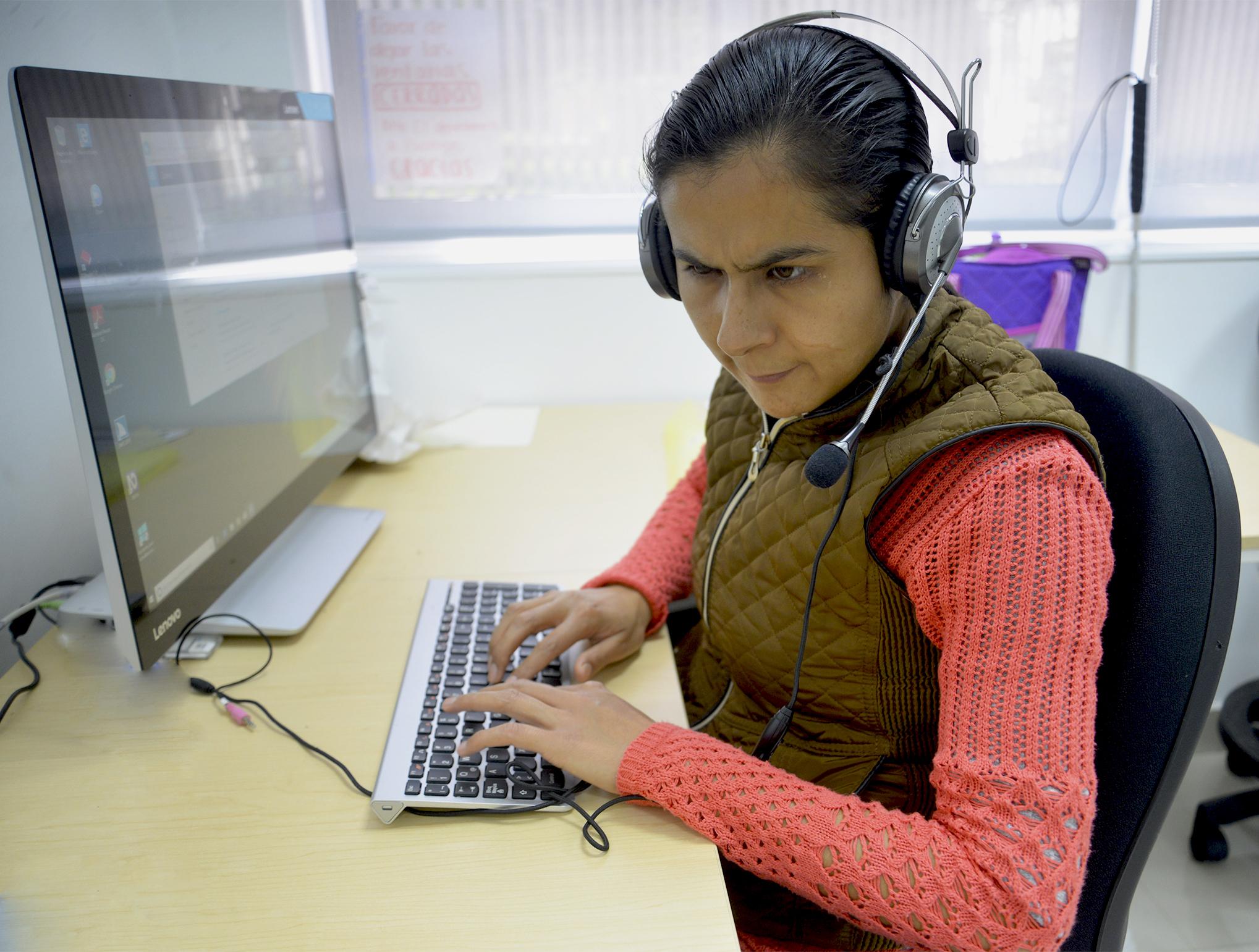 Maribel Flores usando su computadora con uso de audífonos