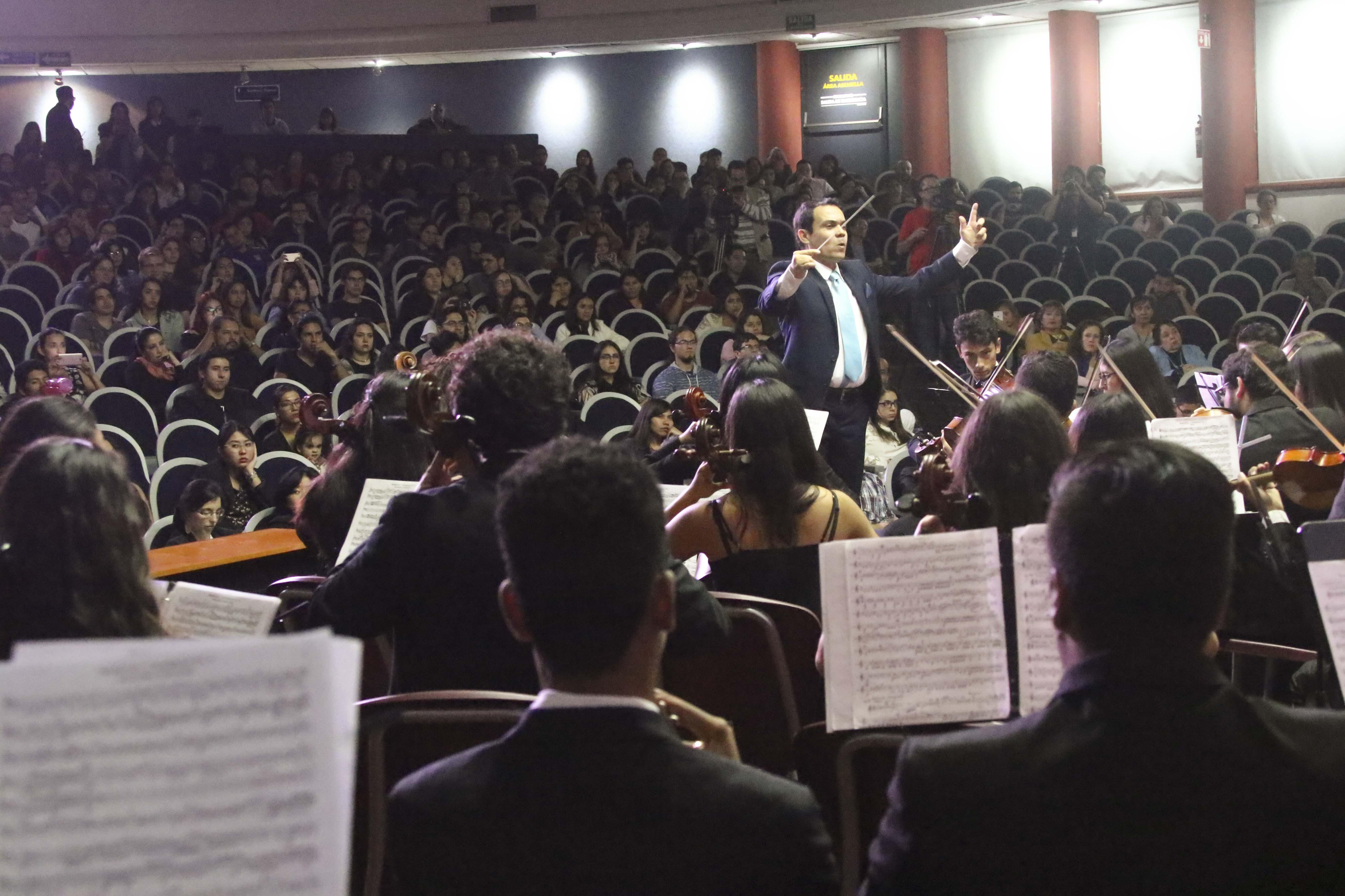 Músicos en pleno concierto. Director al fondo alzando la batuta