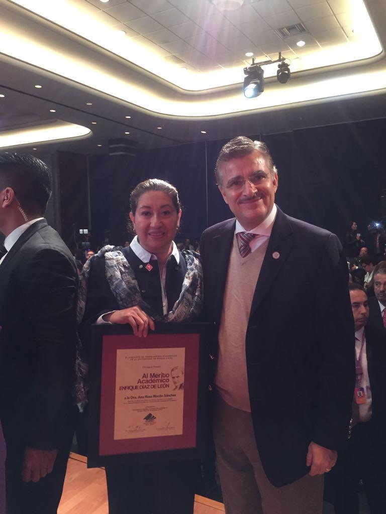 Dra.Ana Rosa Rincón posa exhibiendo su presea con el Rector General de la UdeG