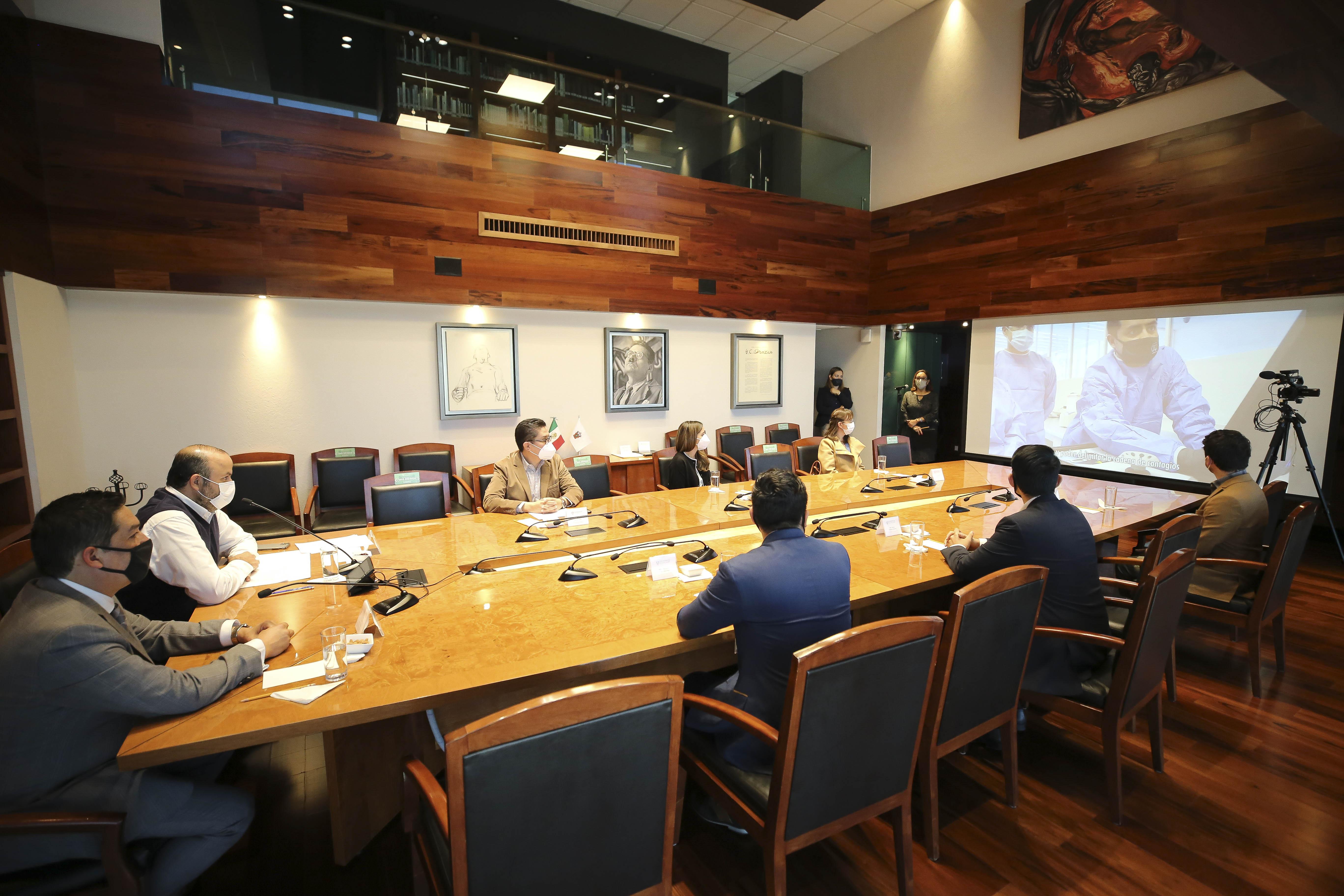 Funcionarios y directivos en sesión en la Sala Clemente Orozco, observan un video