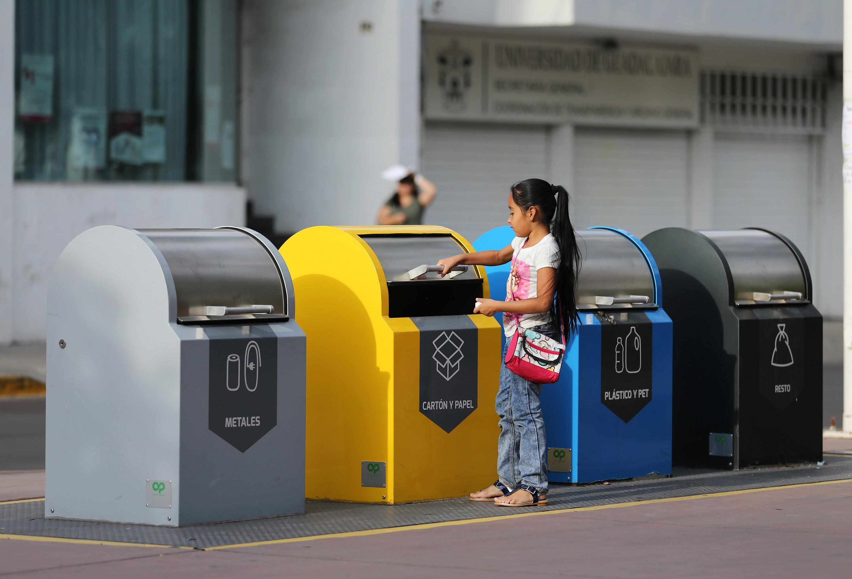 Contenedores de colores para seprar la basura, una niña depositando desechos en uno de ellos