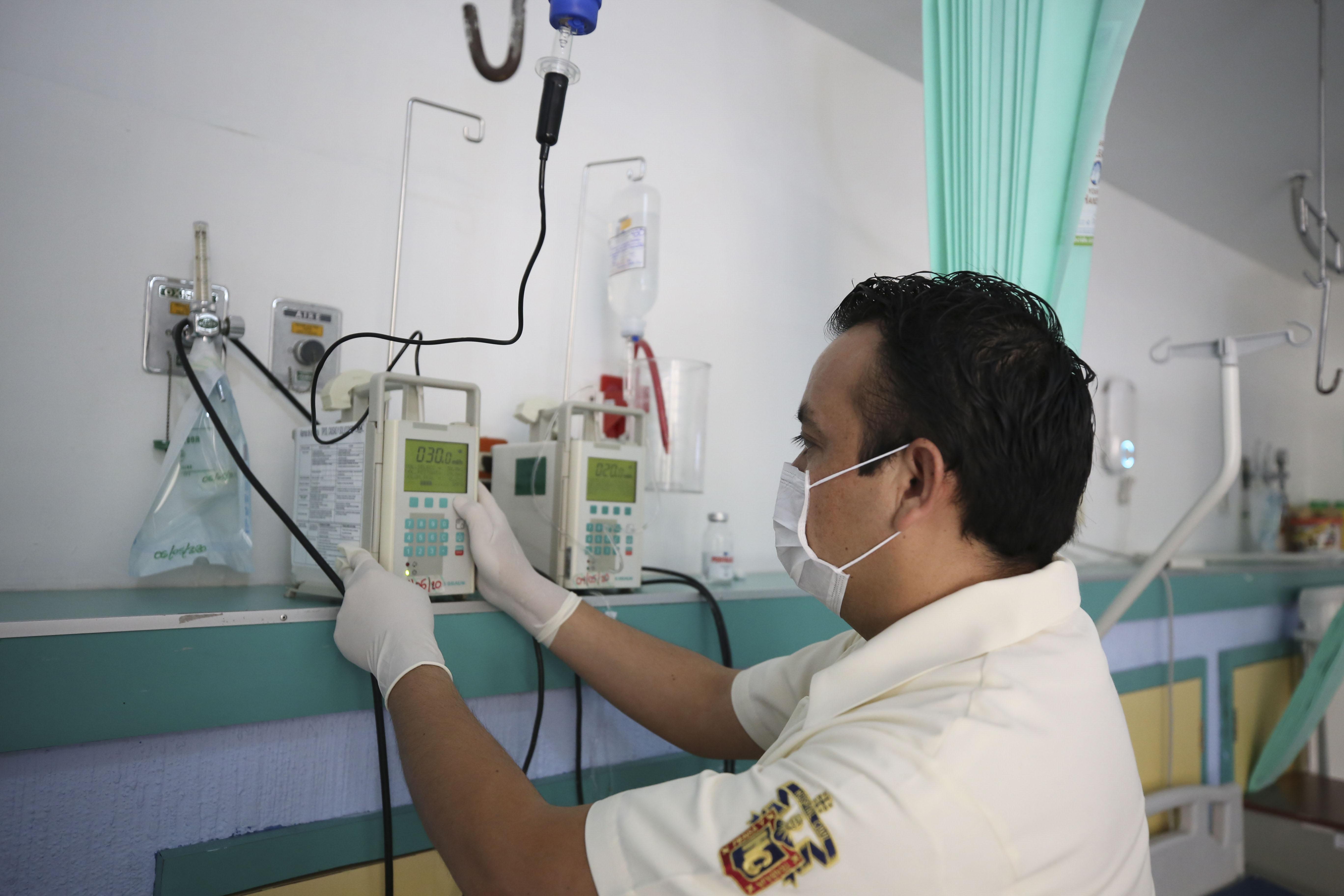 Un enfermero de perfil programando un equipo en la habitación de un hospital