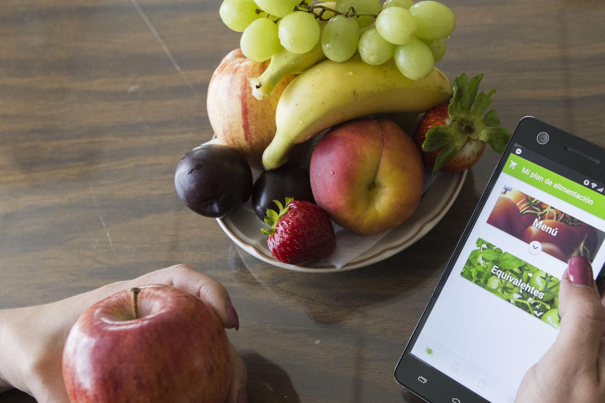 Frutas dispuestas en un plato al lado de un celular en la mano de una mujer en una página que dice menú