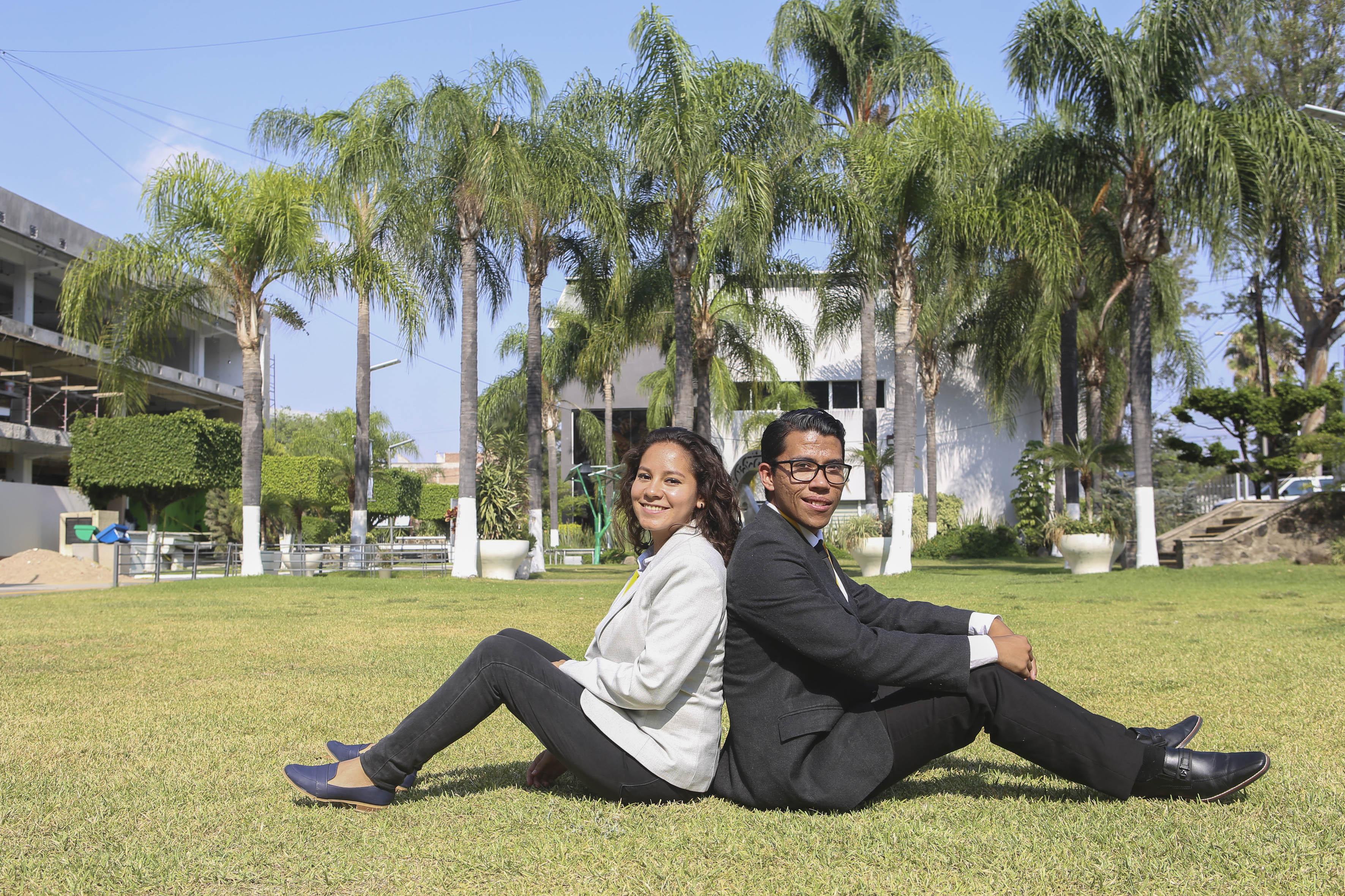 Alumnos sentados recargando sus espaldas entre sí, en jardines de Rectoría