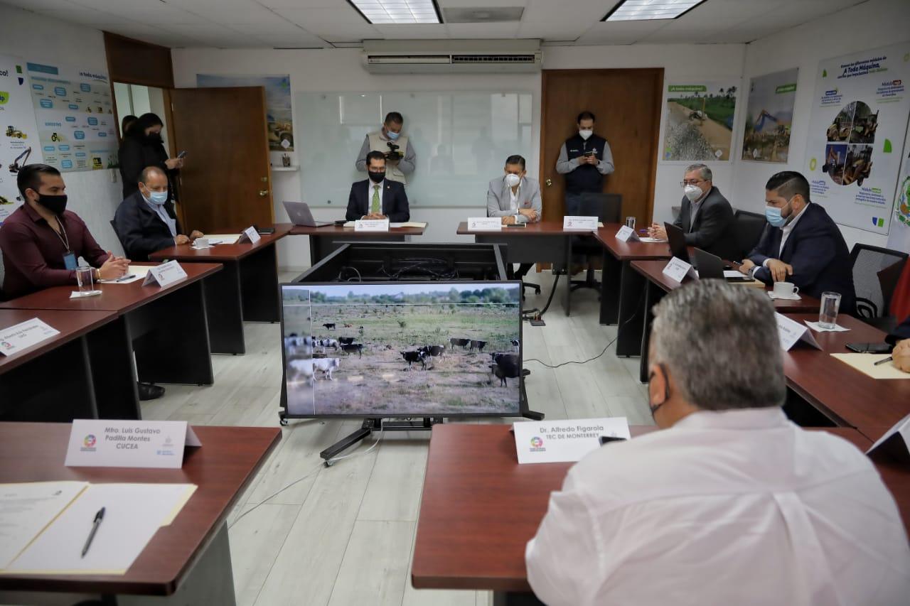 Toma desde atrás del salón de sesiones con funcionarios presentes y computadoras con la sesión virtual