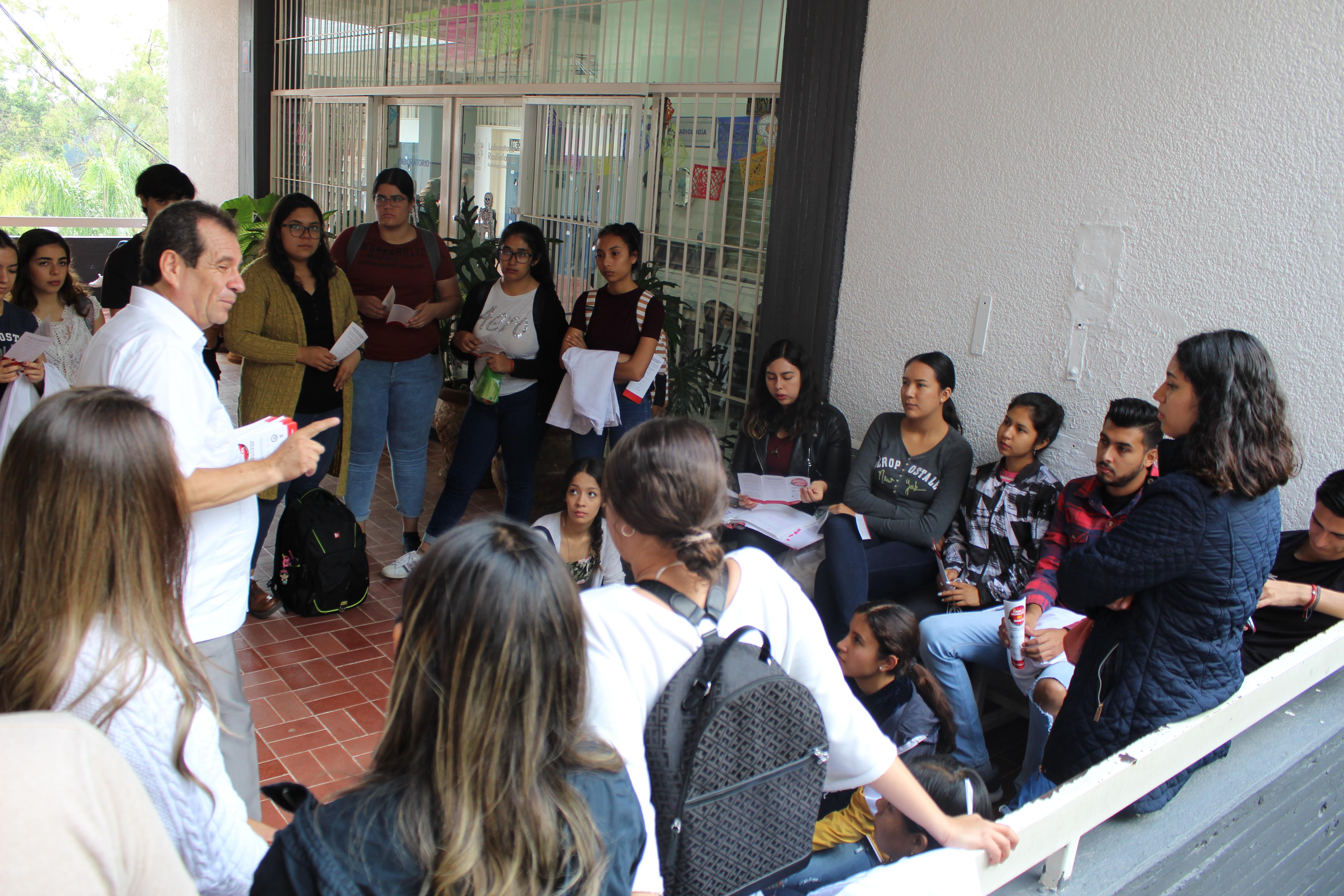 Diputado hablando de su campaña con alumnos sentados en el suelo en uno de los pasillos de Odontología