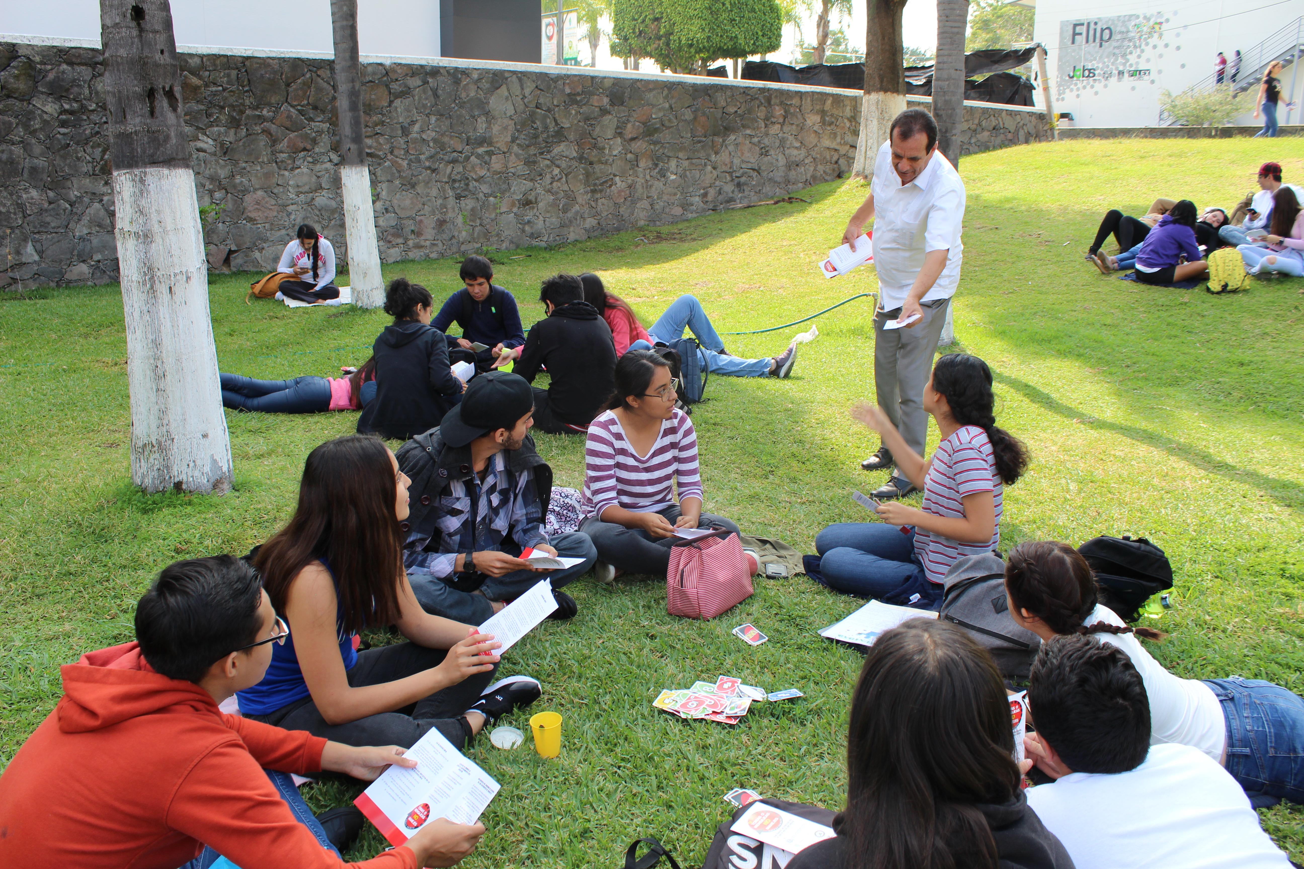 Diputado hablando de su campaña con alumnos reunidos en uno de los jardines