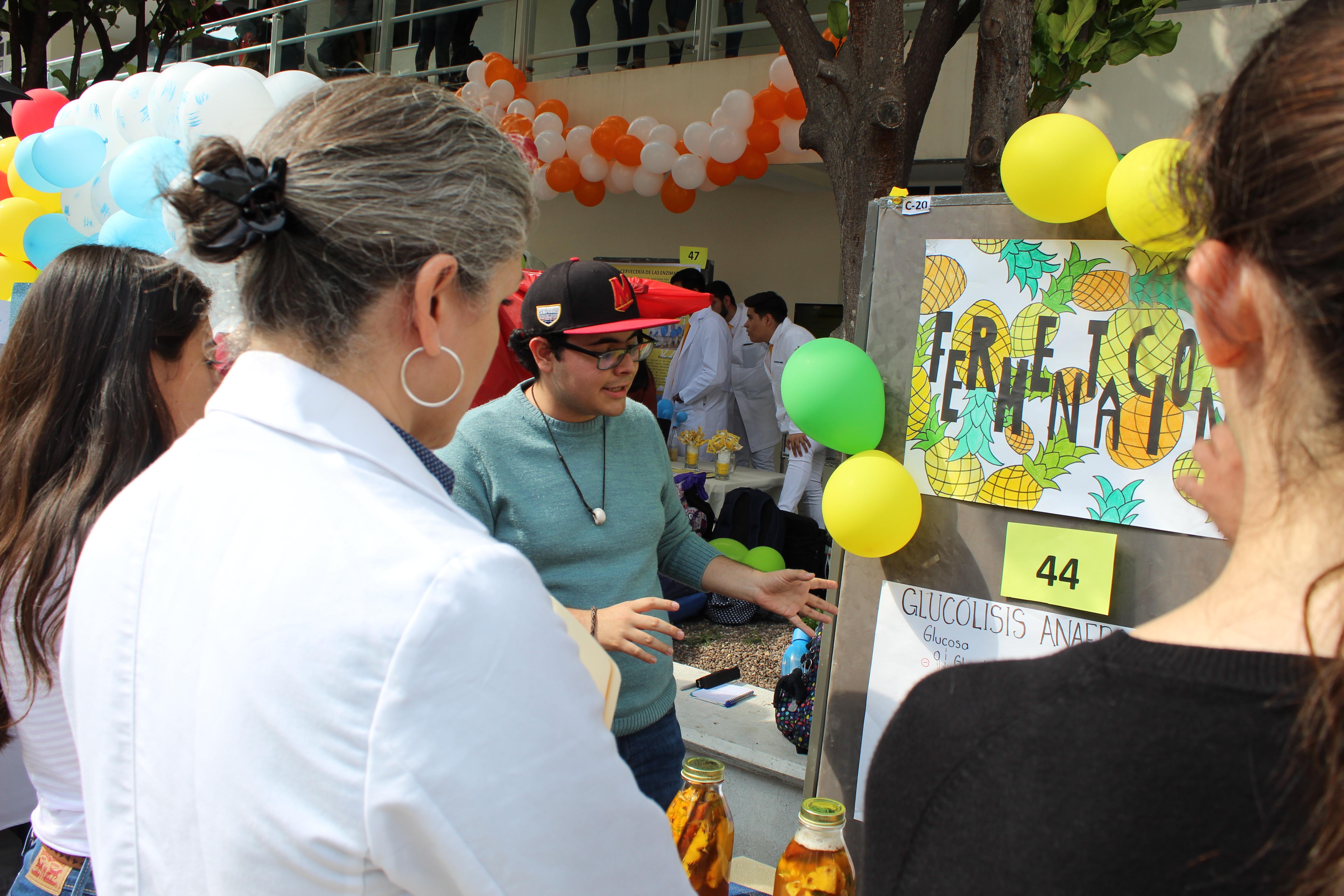 Profesora y alumna leyendo información en un stand