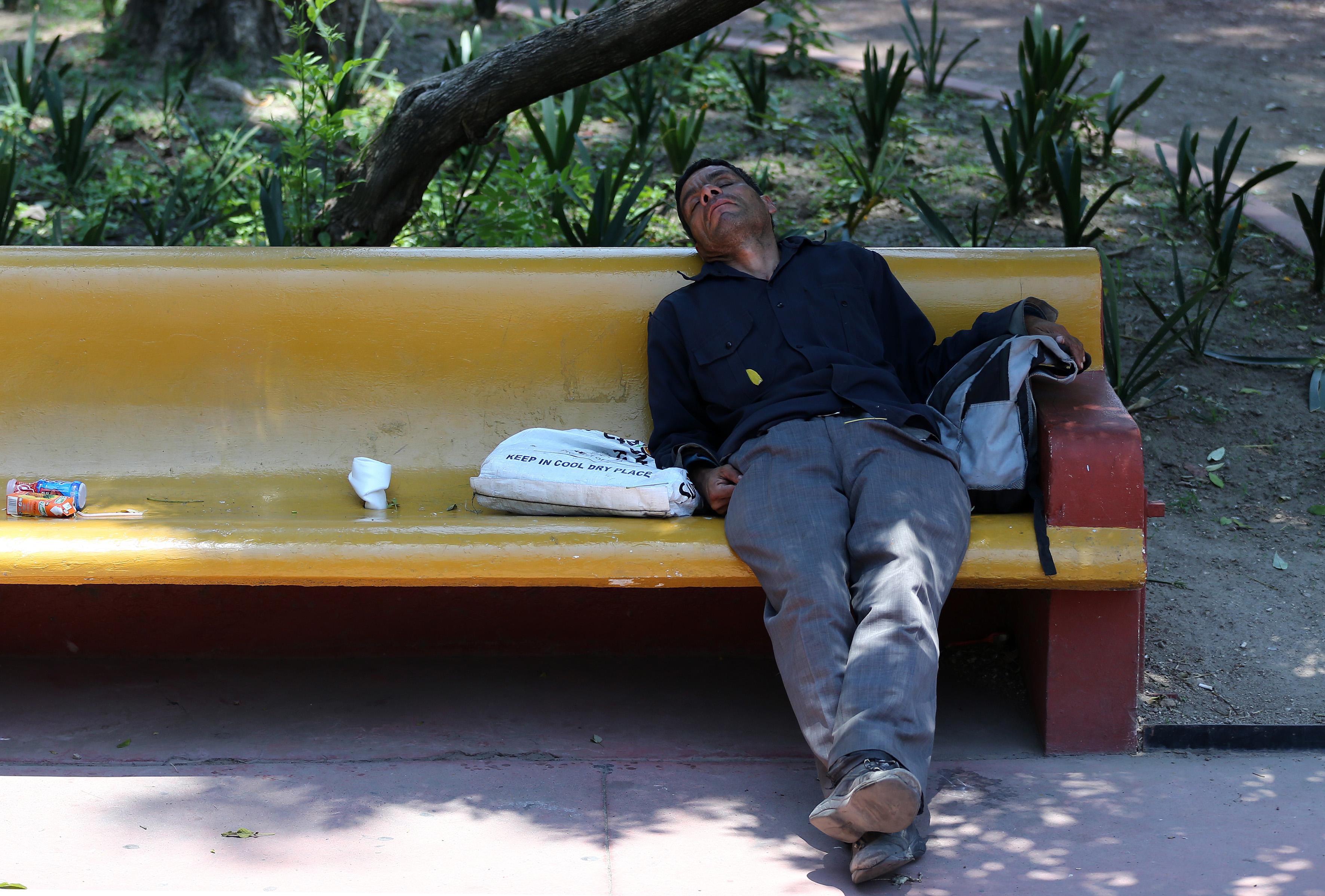 Indigente joven durmiendo en la banca de un parque