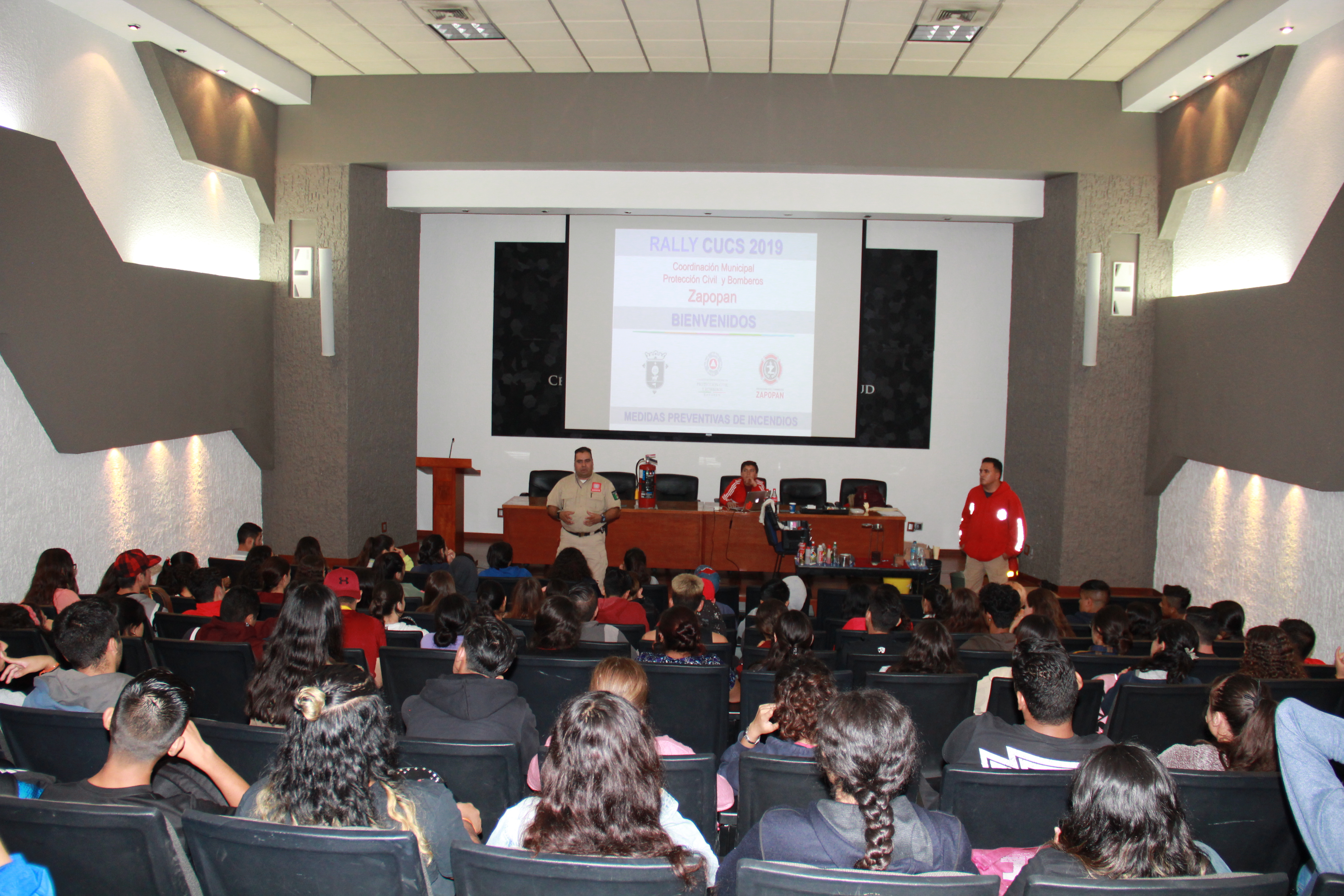 Auditorio lleno de alumnos recibiendo plática de protección civil