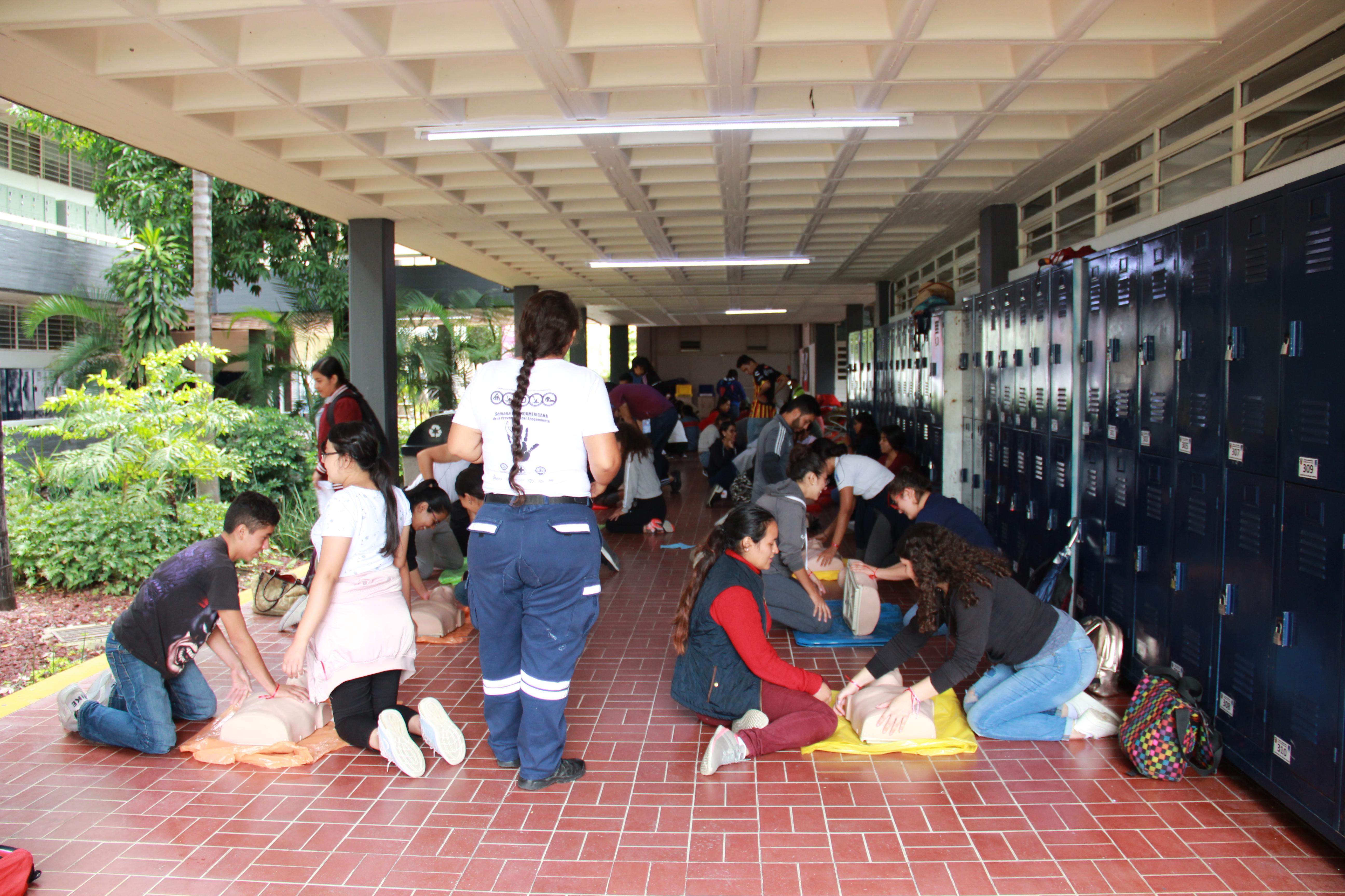 Voluntaria de protección civil instruyendo a alumnos en reanimación cardiopulmonar