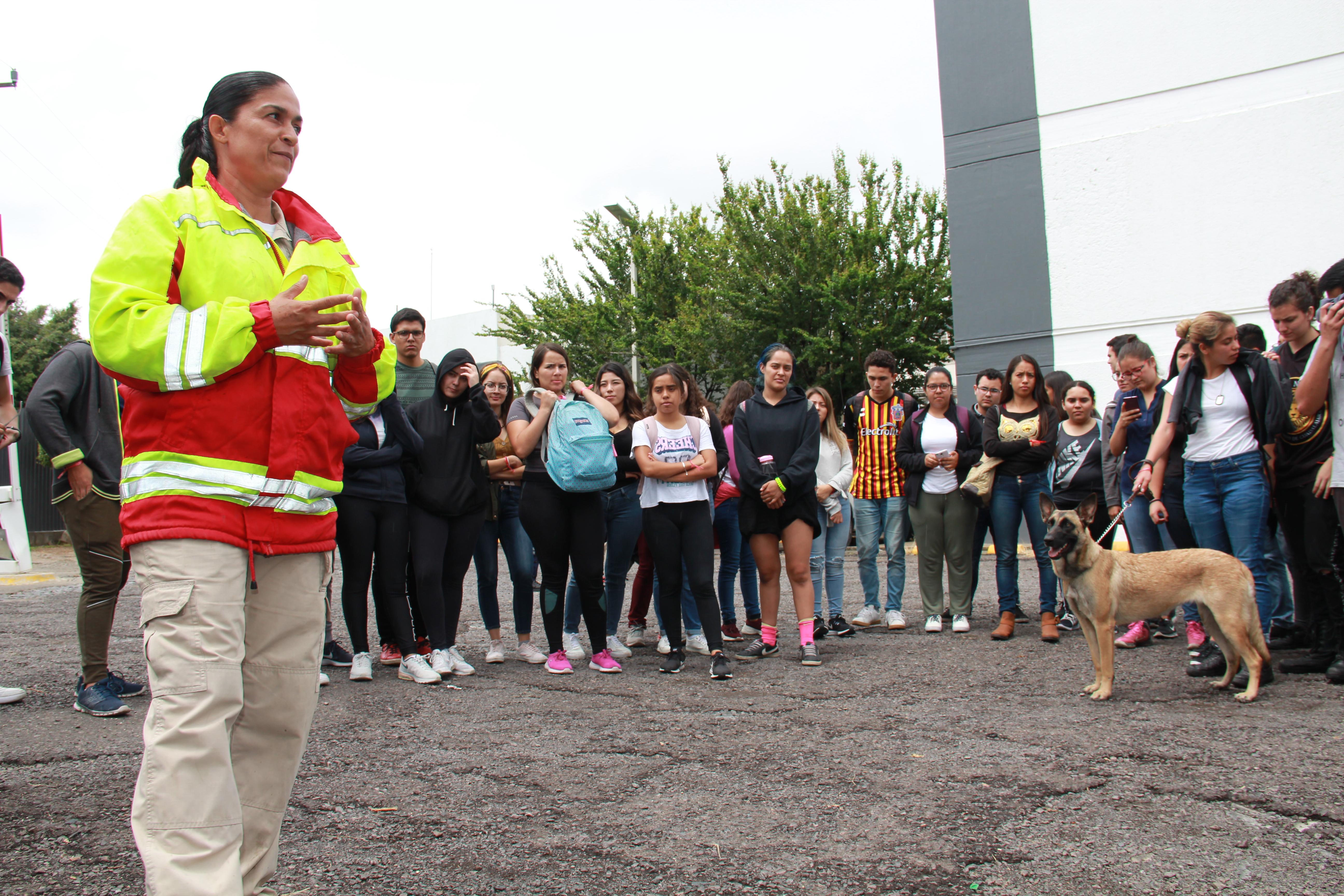 Elemento de protección civil ofreciendo plática de binomio canino a estudiantes