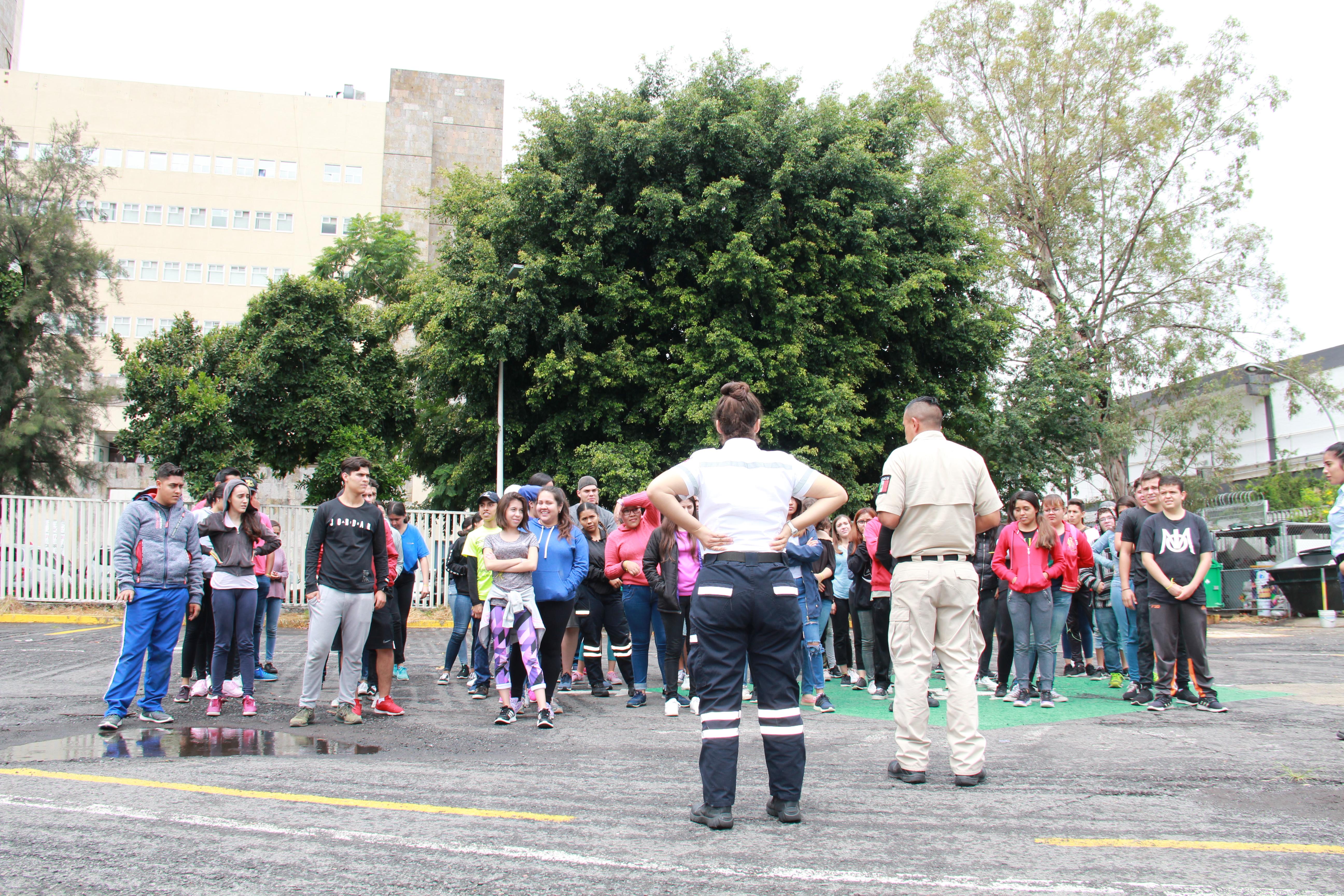 Voluntaria de protección civil organizando a un grupo de estudiantes en uno de los estacionamientos
