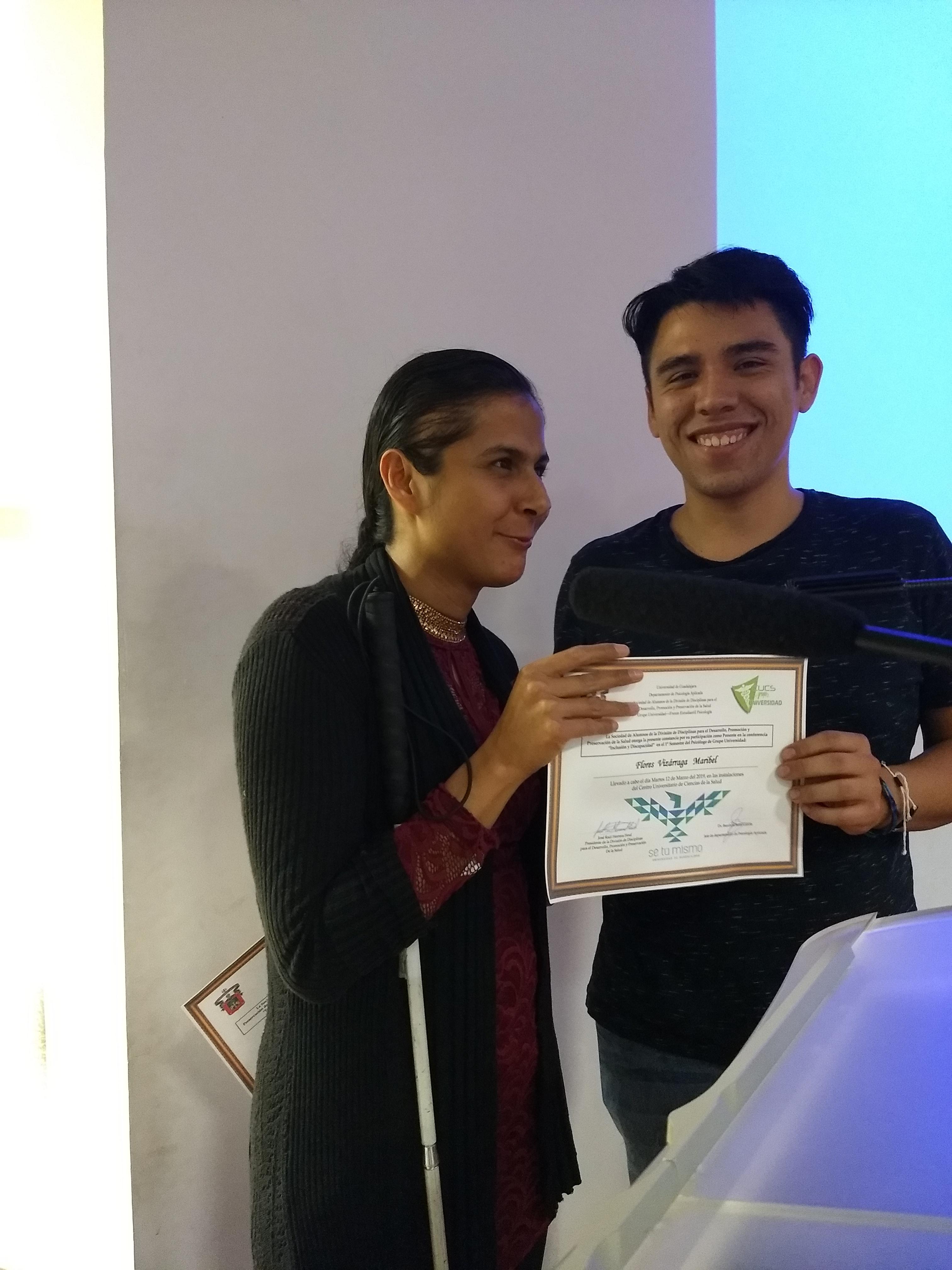 Jefa de la Unidad de Inclusión y el representante de los alumnos exhibiendo el reconocimiento entregado