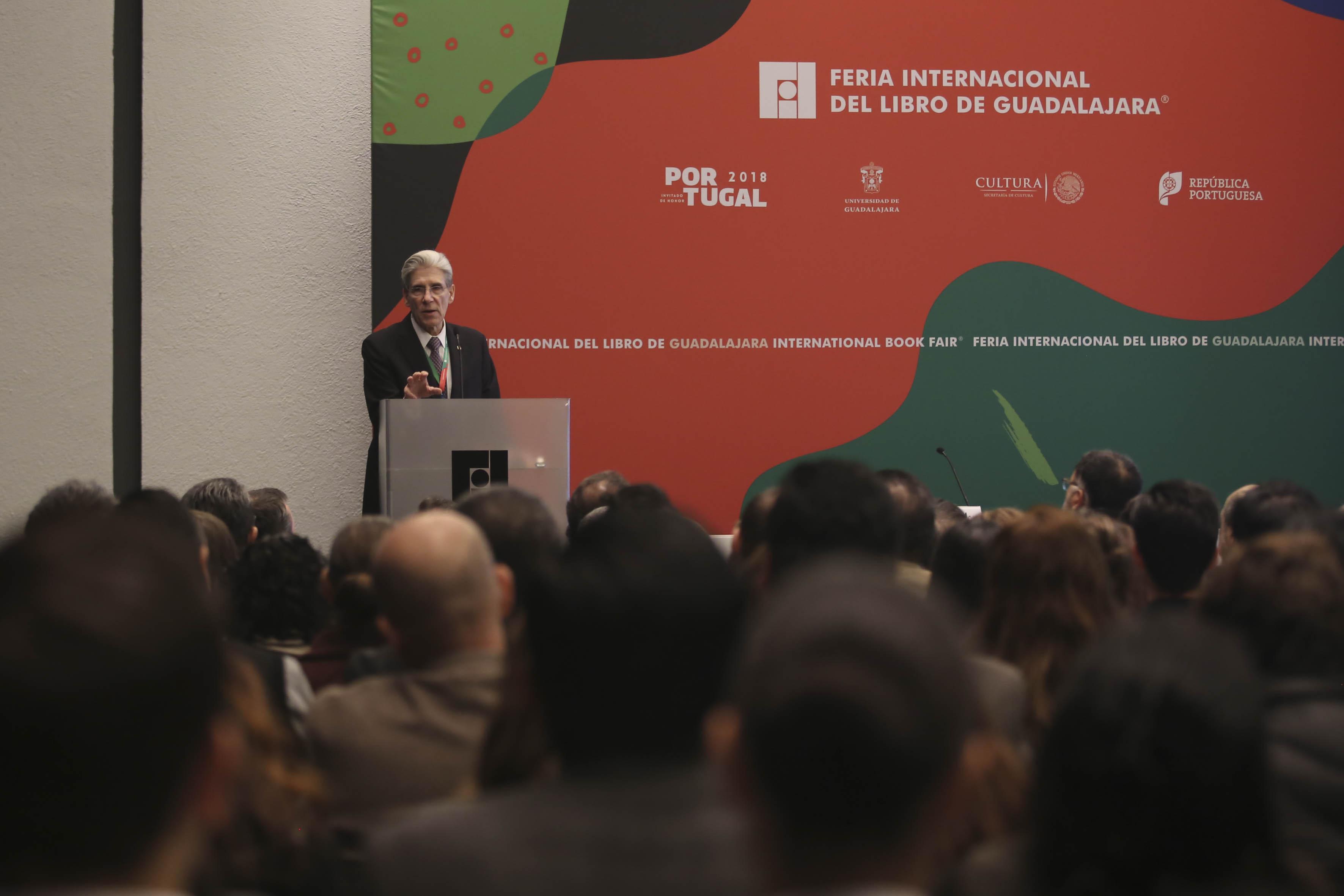 Dr. Julio Frenk al fondo del salón, antes se ven personas sentadas en un salón a lleno total