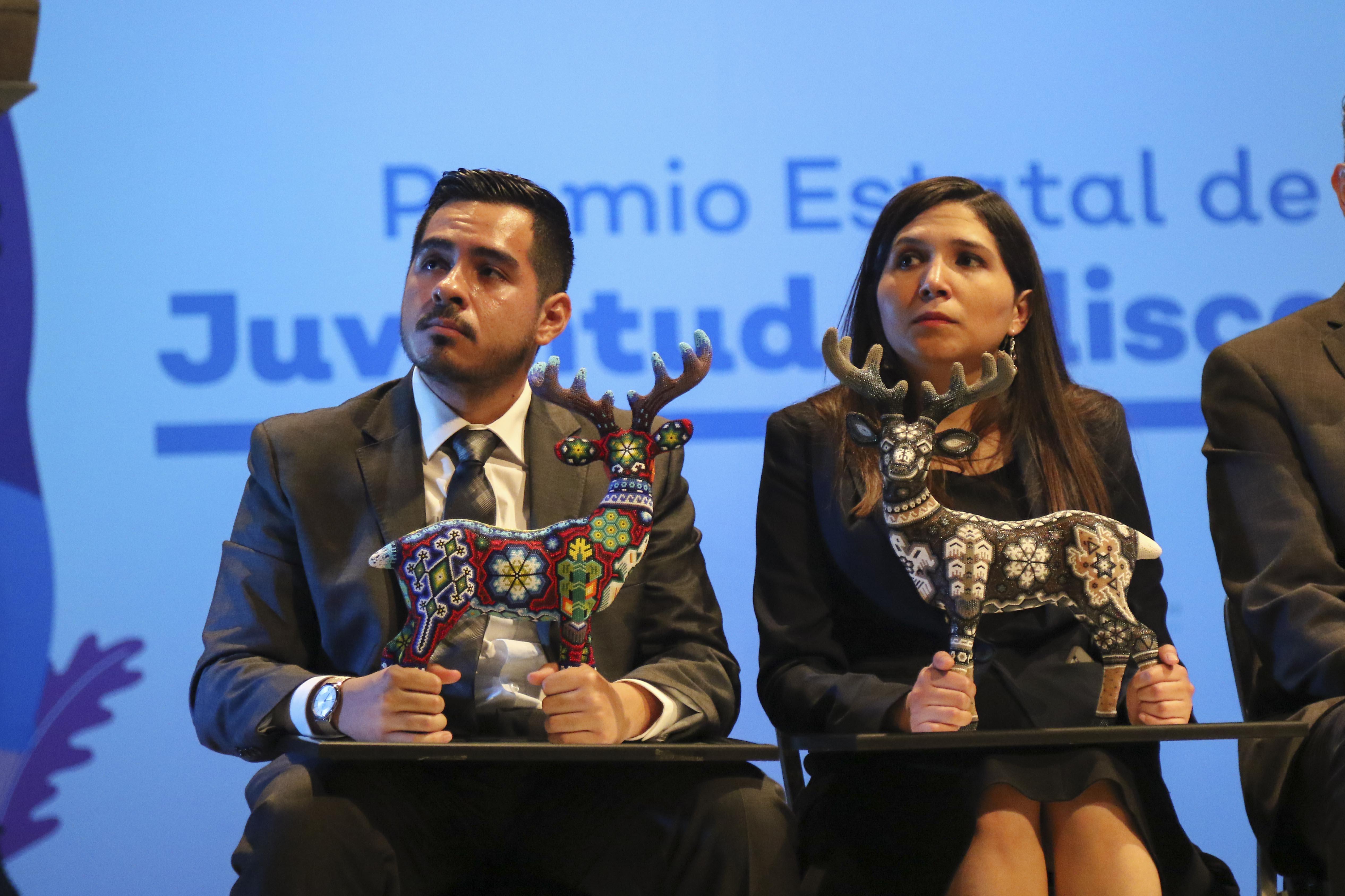 Egresados de UdeG escuchando al ponente, tienen en sus manos el galardón con el que los premiaron