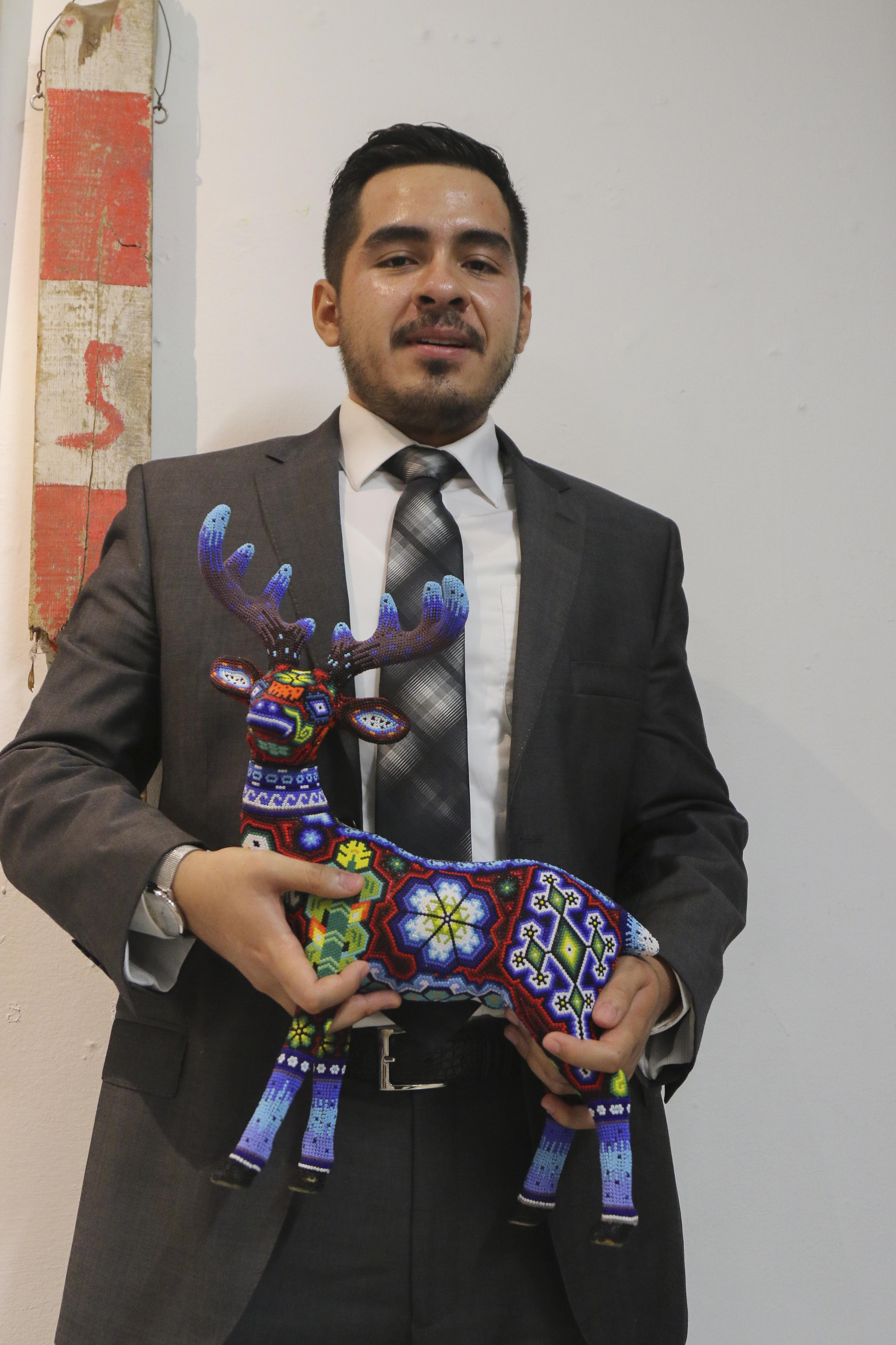 Iván Segura Durán posa para la foto, tiene en las manos la estatuilla artesanal con la que lo distinguieron