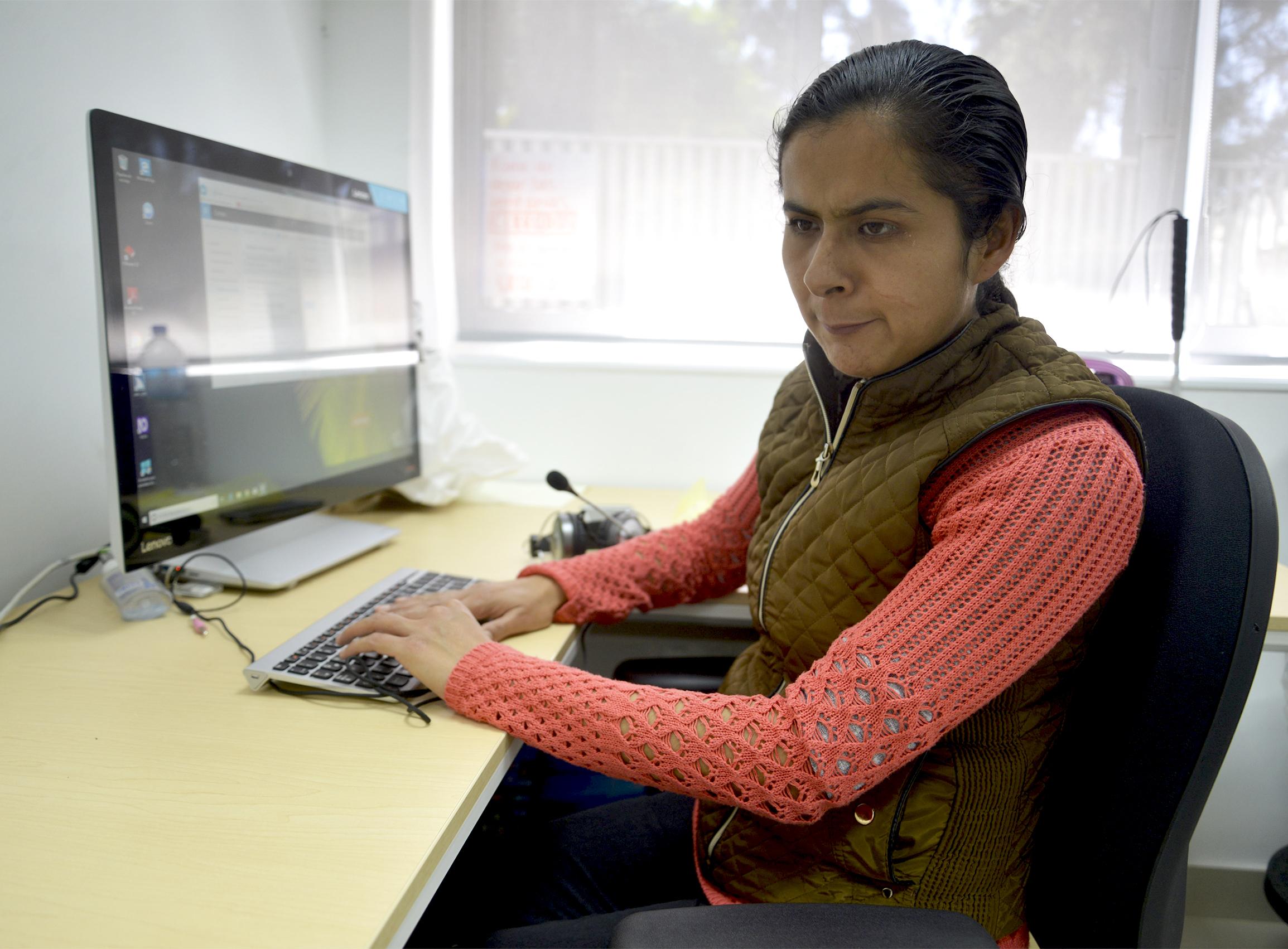 Maribel Flores usando su computadora con sonido en altavoz
