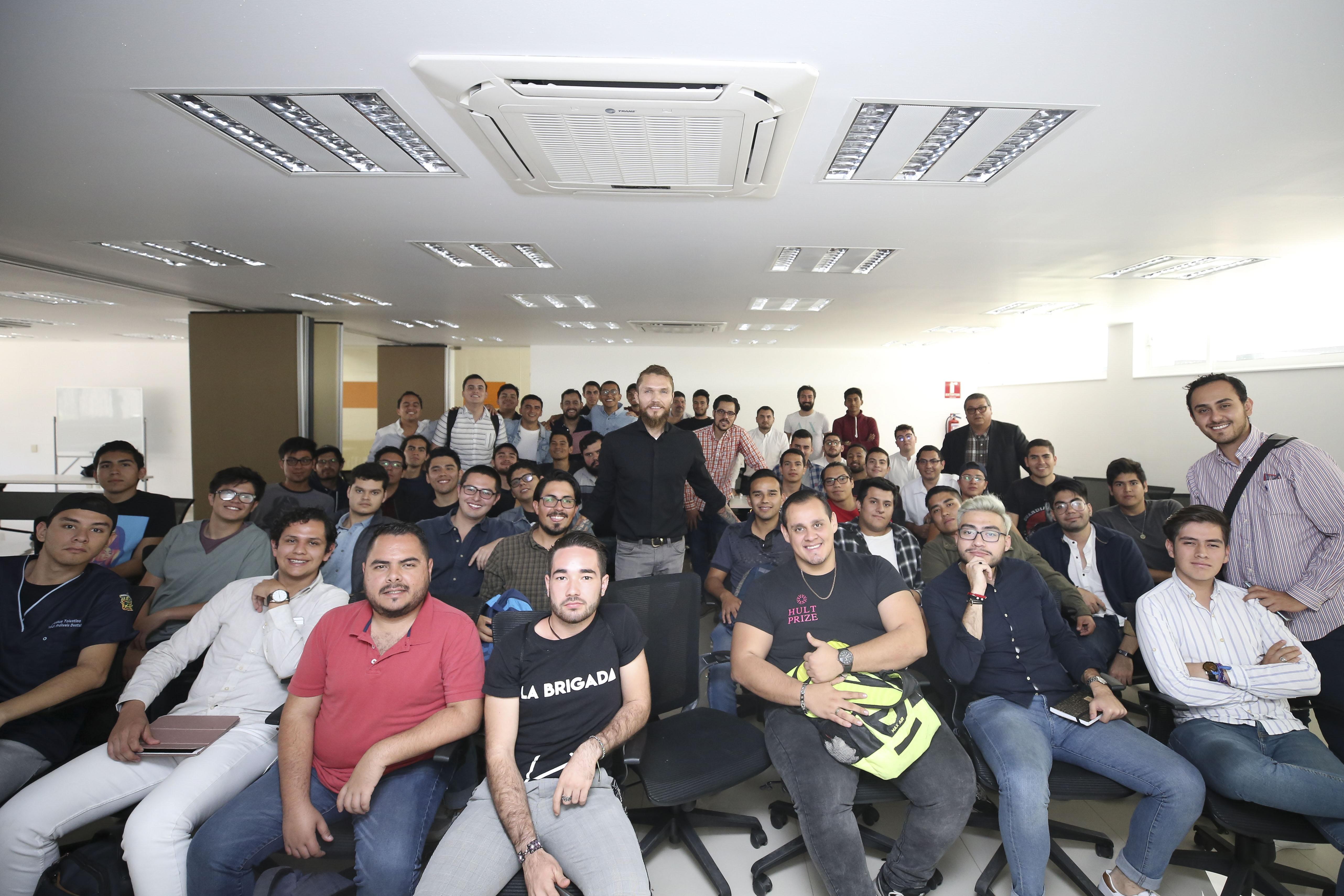 Foto grupal de participantes en el grupo, al centro uno de los ponentes