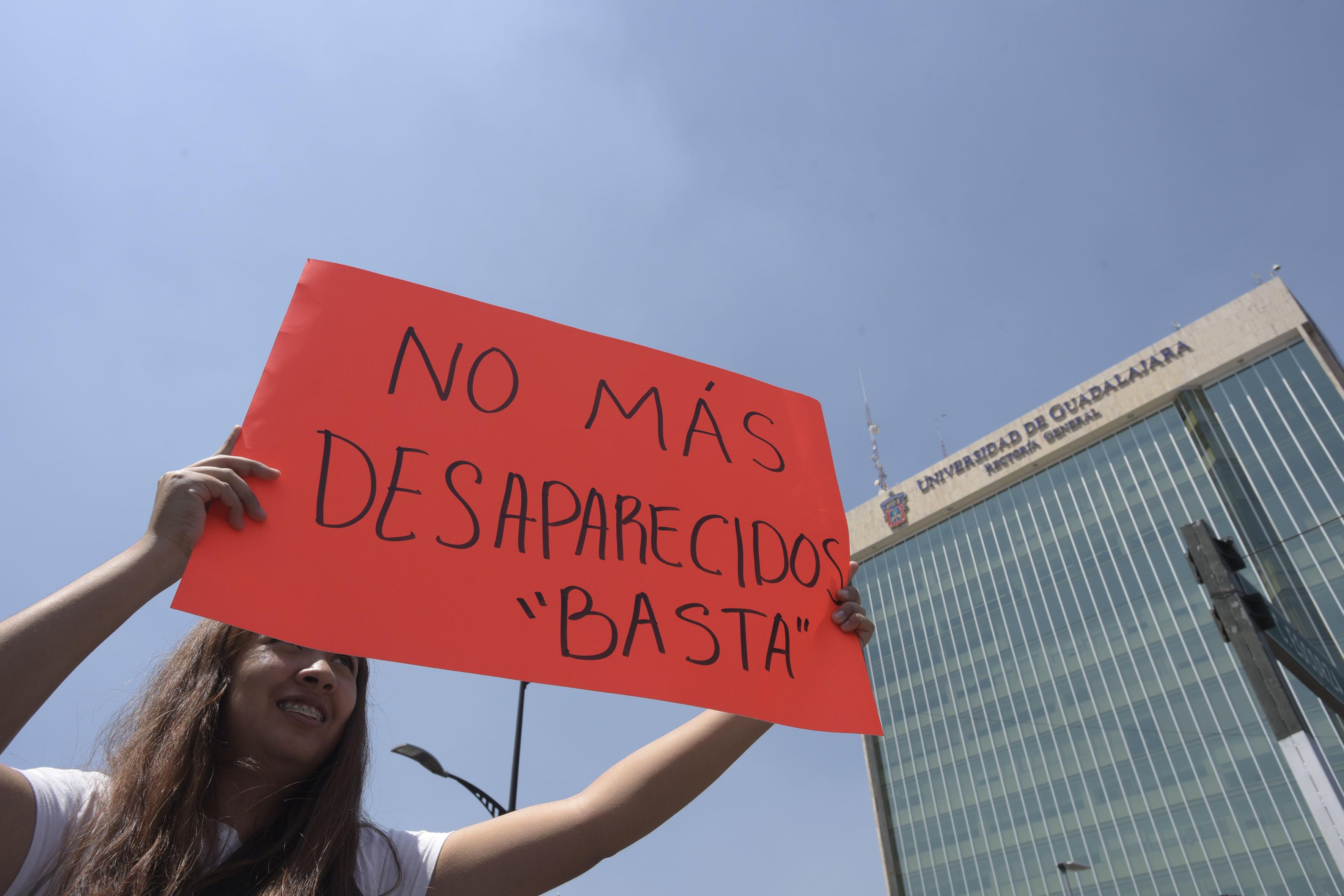 Estudiate exhibiendo letrero de protesta, al fondo edificio de Rectoría General