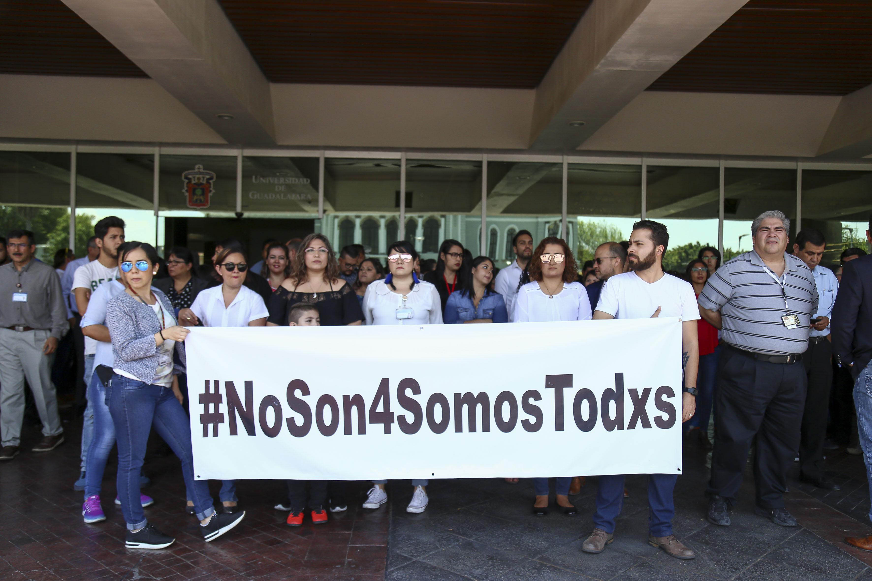 Foto a las puertas del edificio de Rectoría General con alumnos, trabajadores, docentes y funcionarios exhibiendo una manta de protesta