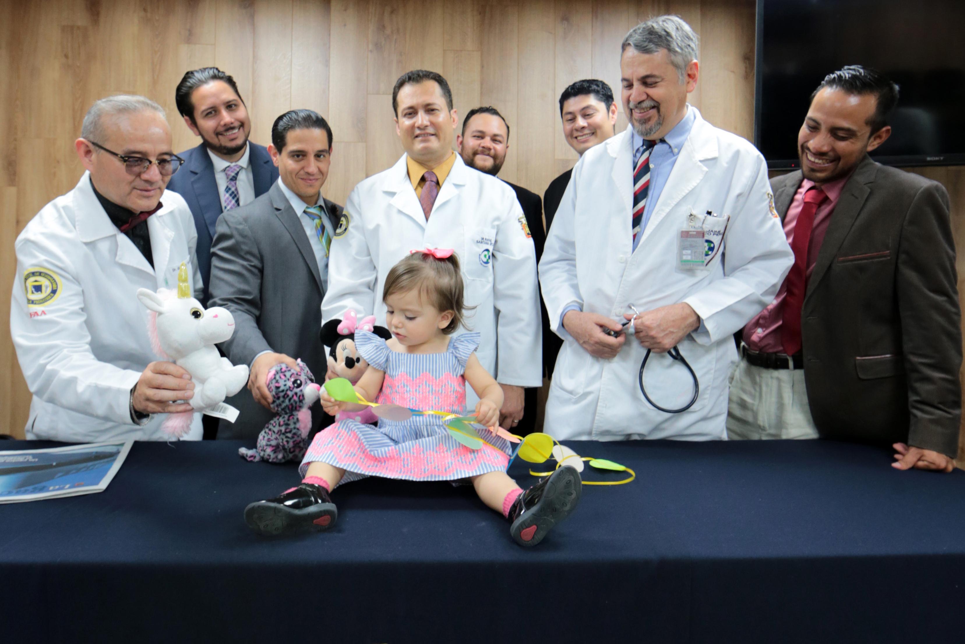 Médicos cirujanos pediatras posan con paciente