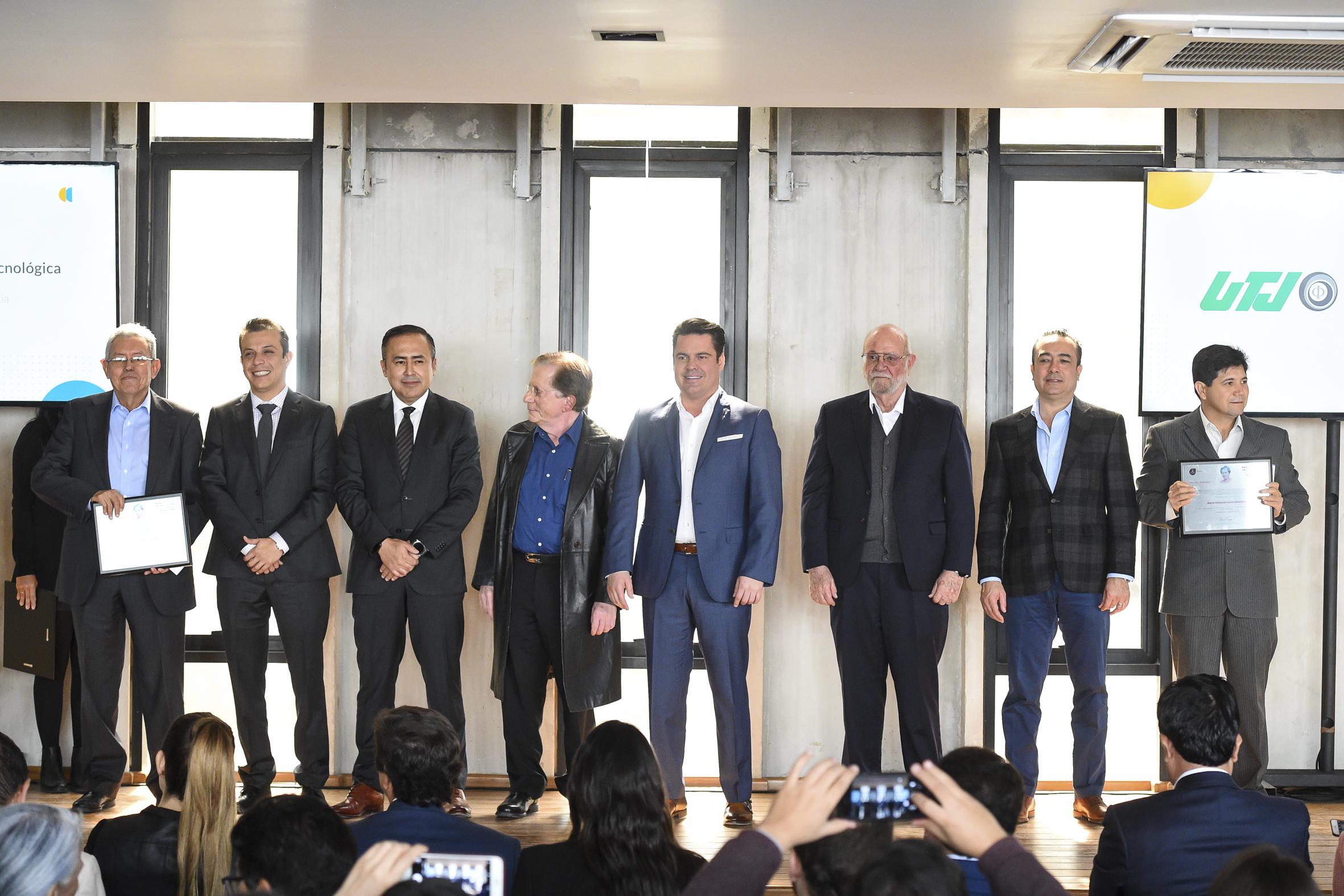 Funcionarios de Gobierno posando para la foto con dos galardonados de UdeG