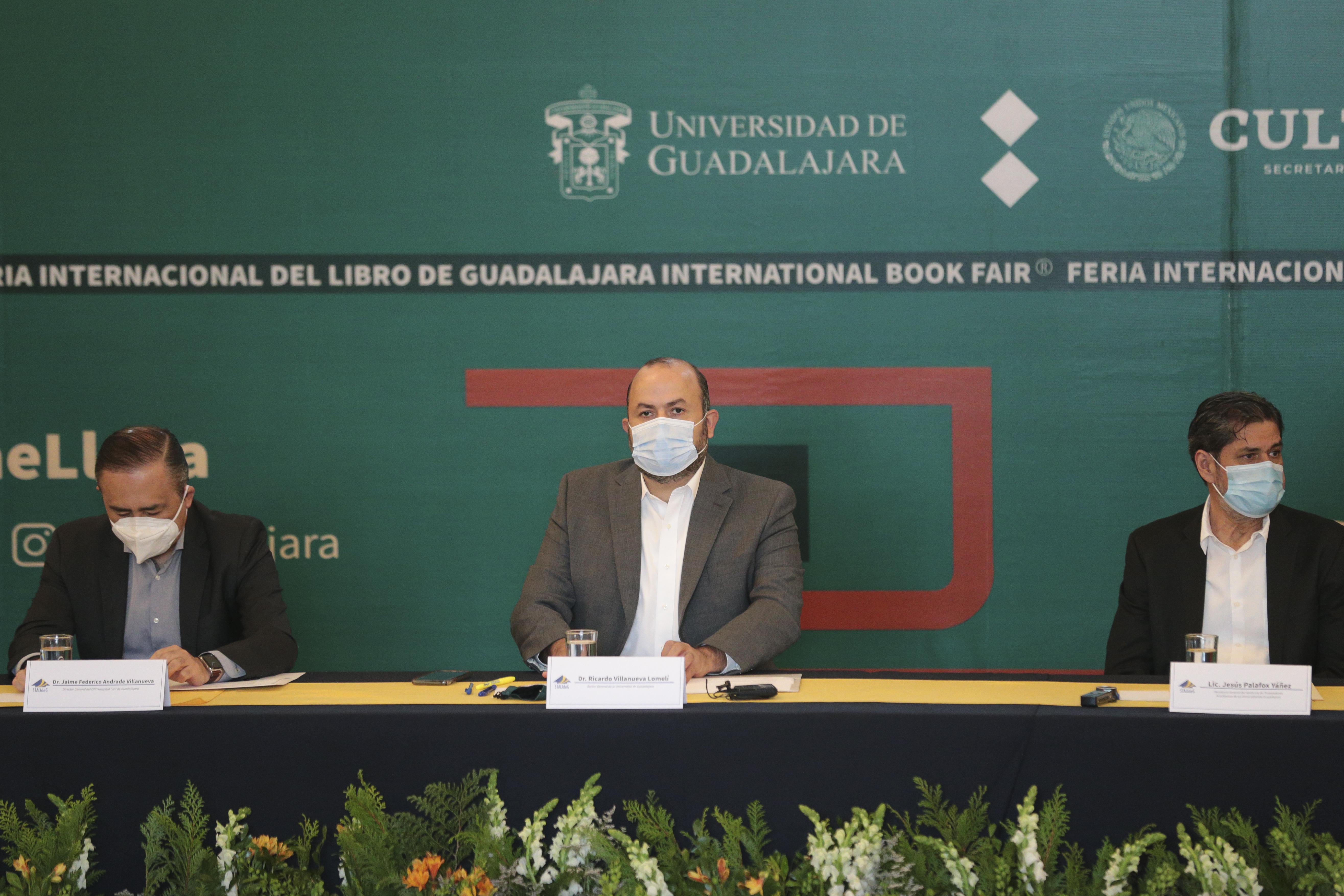 Rector General sentado en la mesa del presídum al centro, el Director de los Hospitales Civiles a su derchos y el Secretario General del STAUdeG a su izquierda
