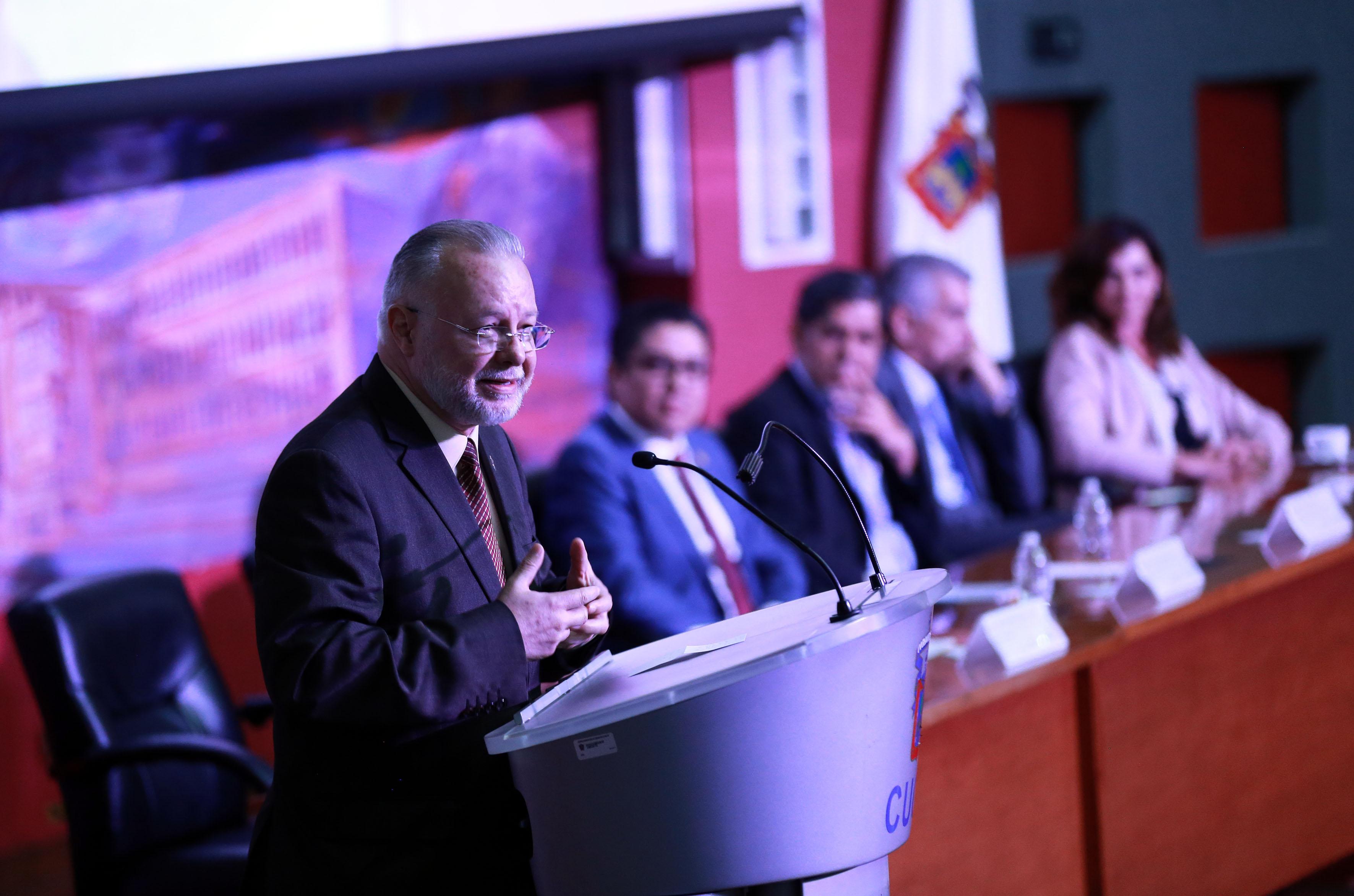 Mtro. Trindad Padilla López, al micrófono en el pódium