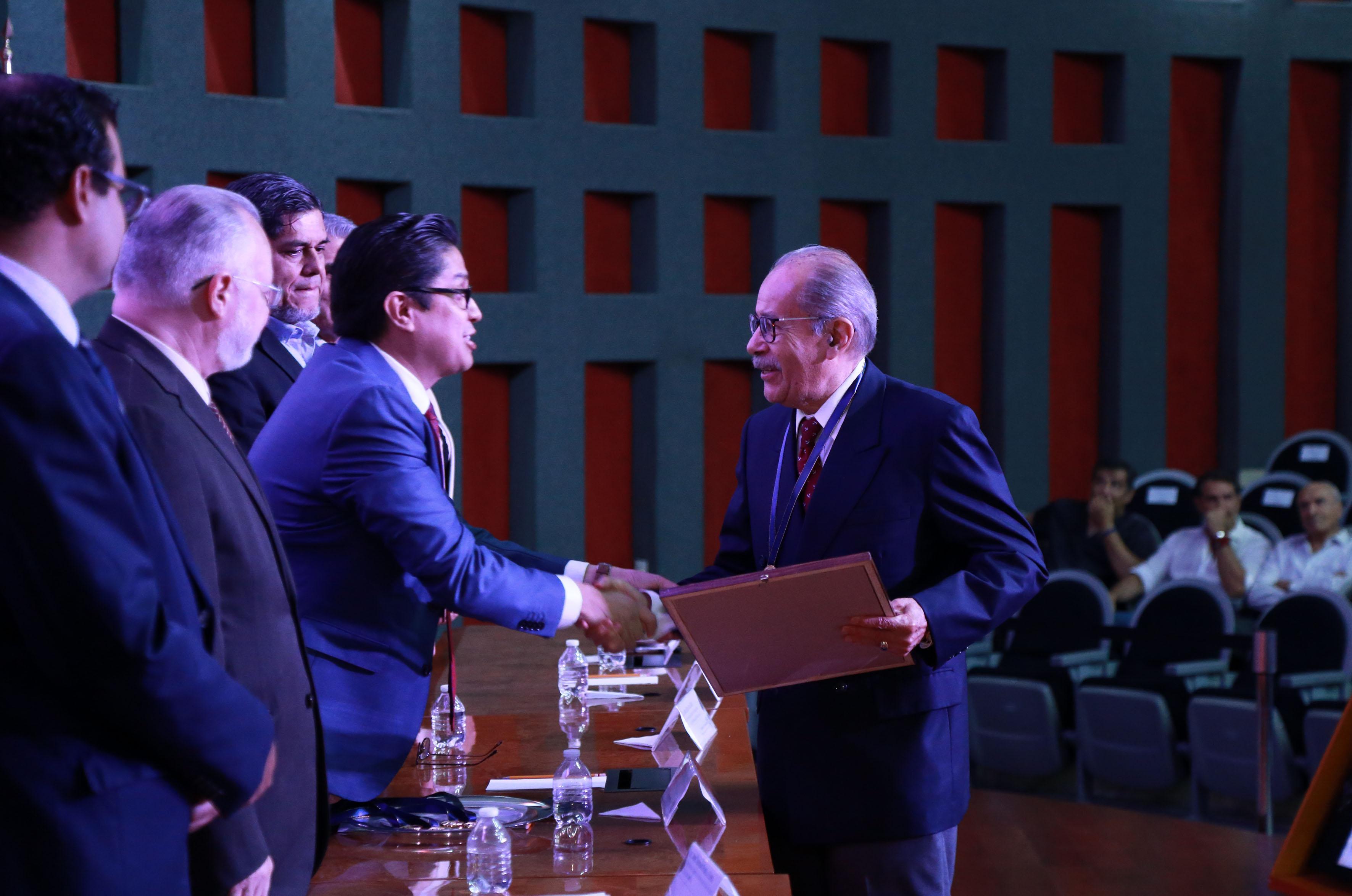 Galardonado recibiendo reconocimiento y medalla de manos del rector