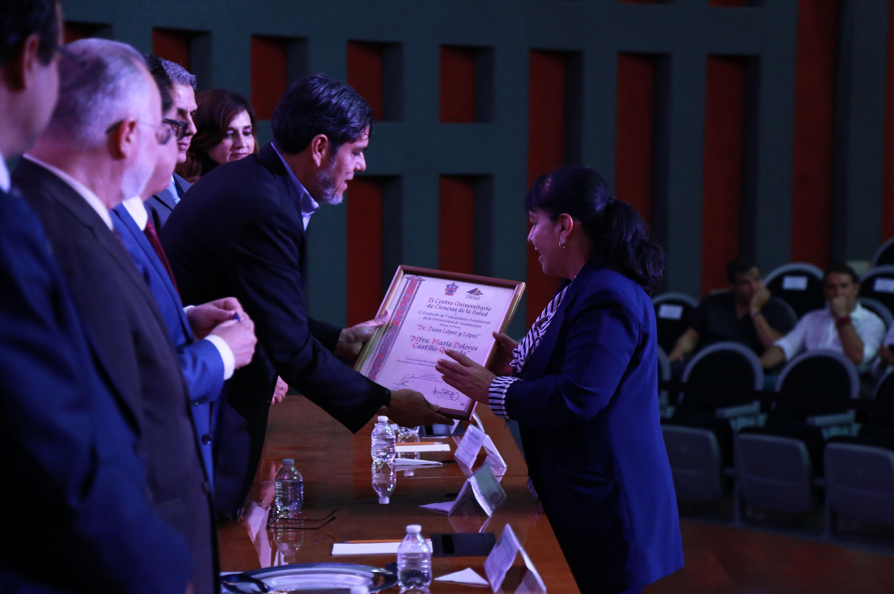 Galardonada recibiendo reconocimiento y medalla de manos del secretario general de STAudeG