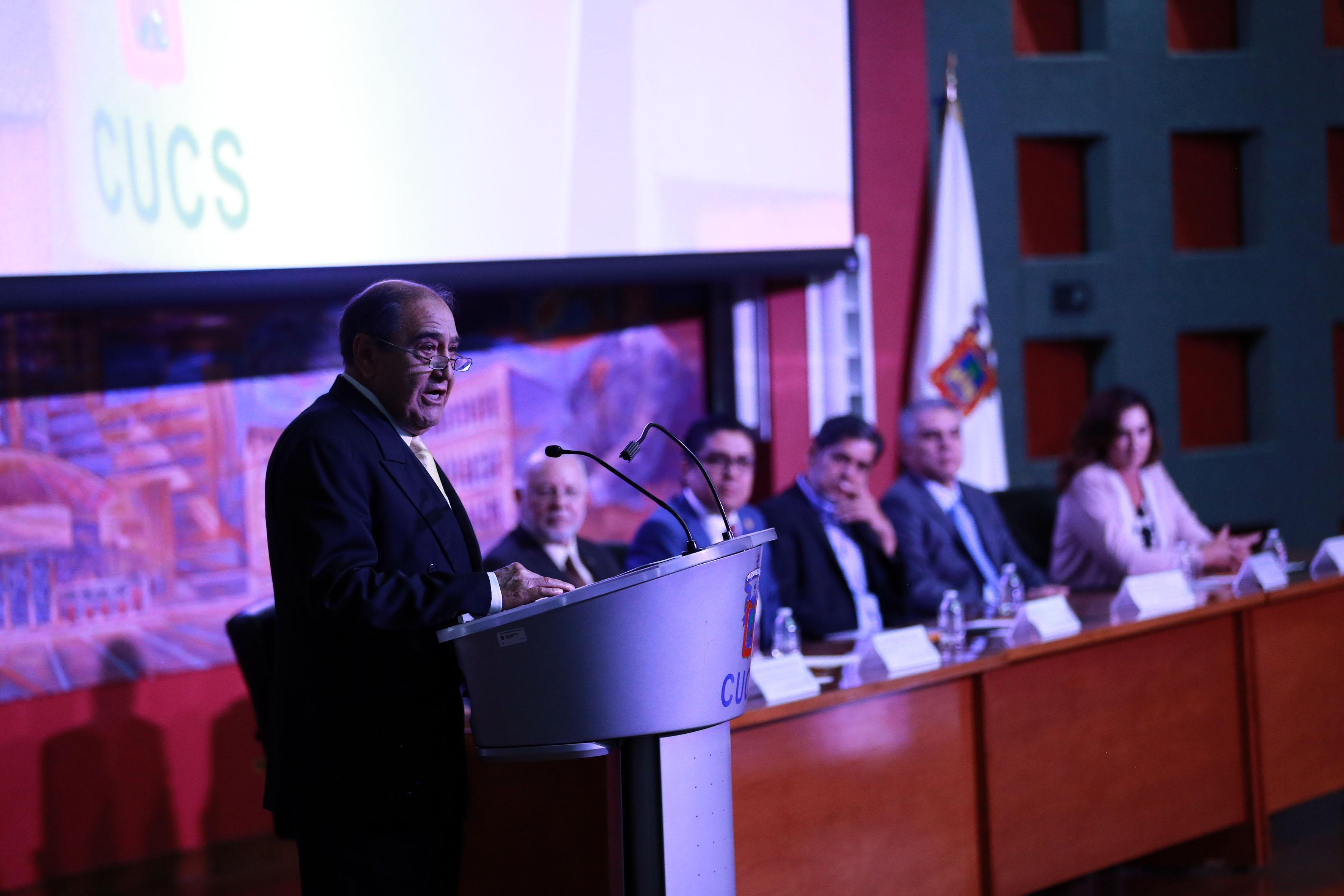 Dr.José Humberto Muñoz López, representante de los galardonados al micrófono en el pódium