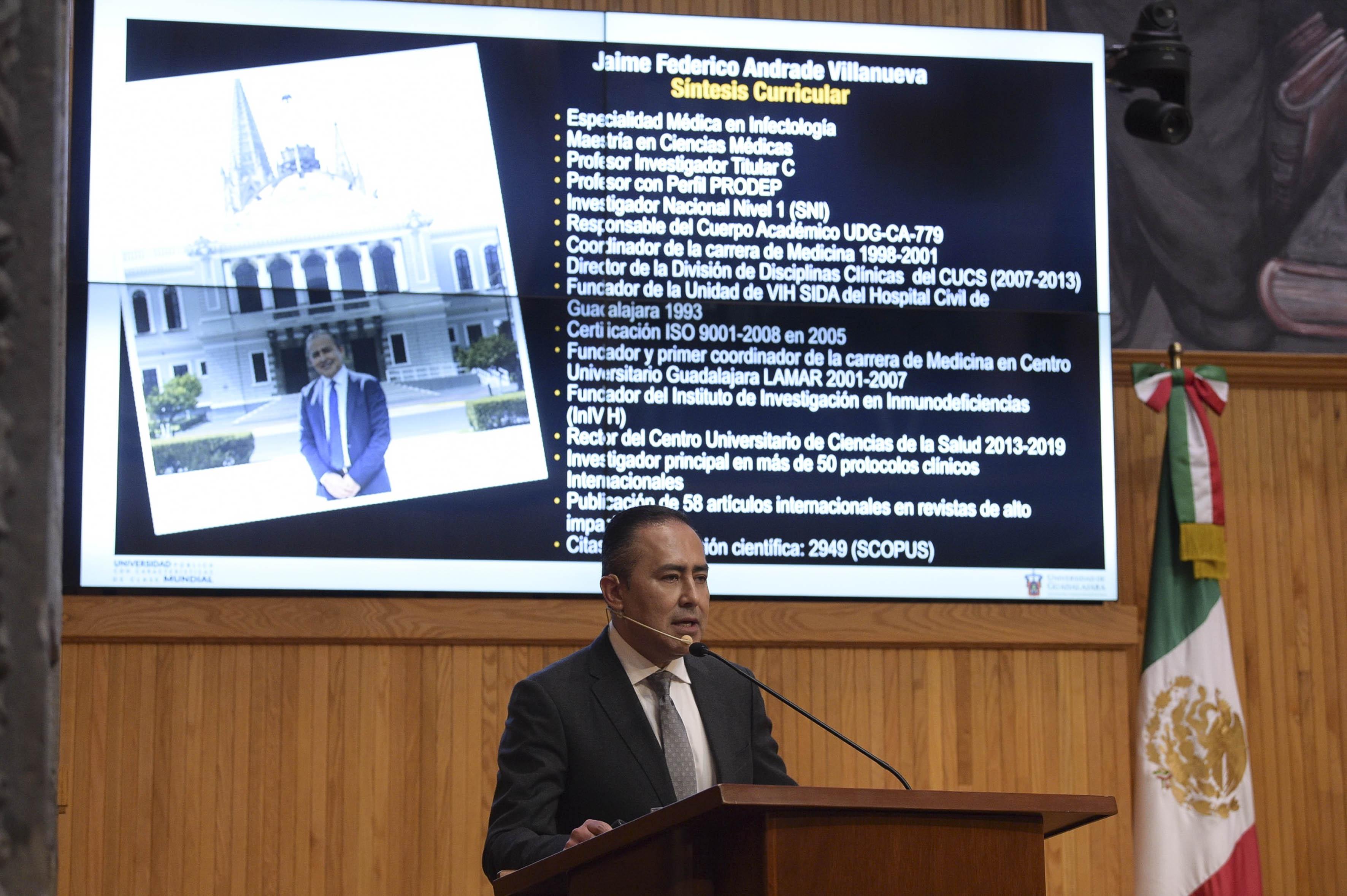 Dr. Jaime Andrade presentando su plan de trabajo, atrás diapositiva en el monitor