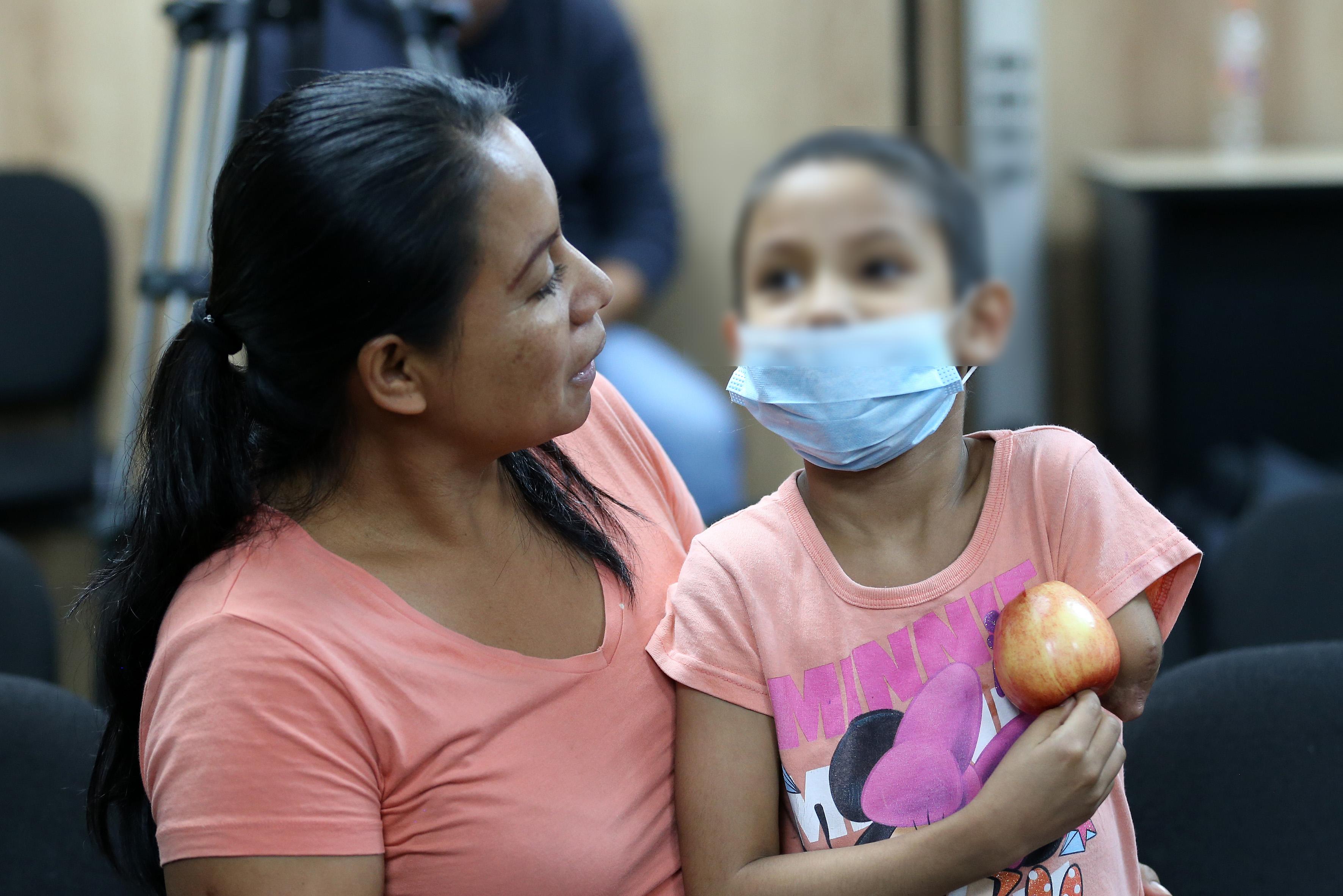 Mamá abrazando a su hija con cáncer, ella con cubrebocas