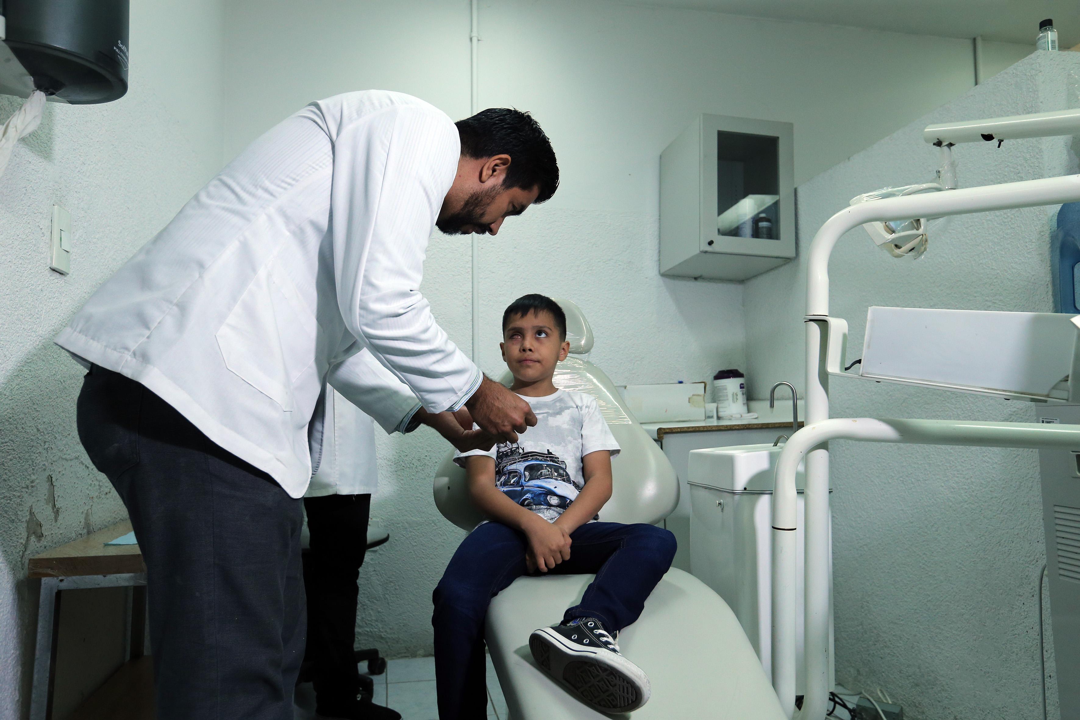 Médico especialista le realiza limpieza en el ojo al niño receptor de prótesis
