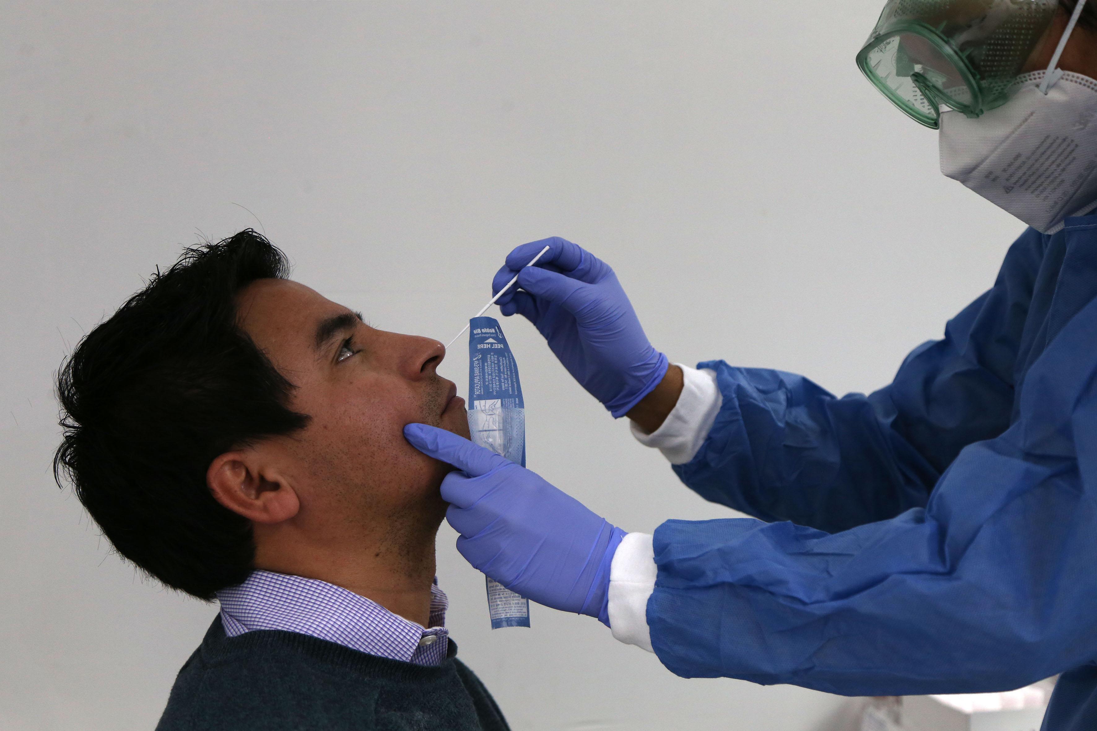 Personal de salud introduciendo isopo en la nariz de un paciente
