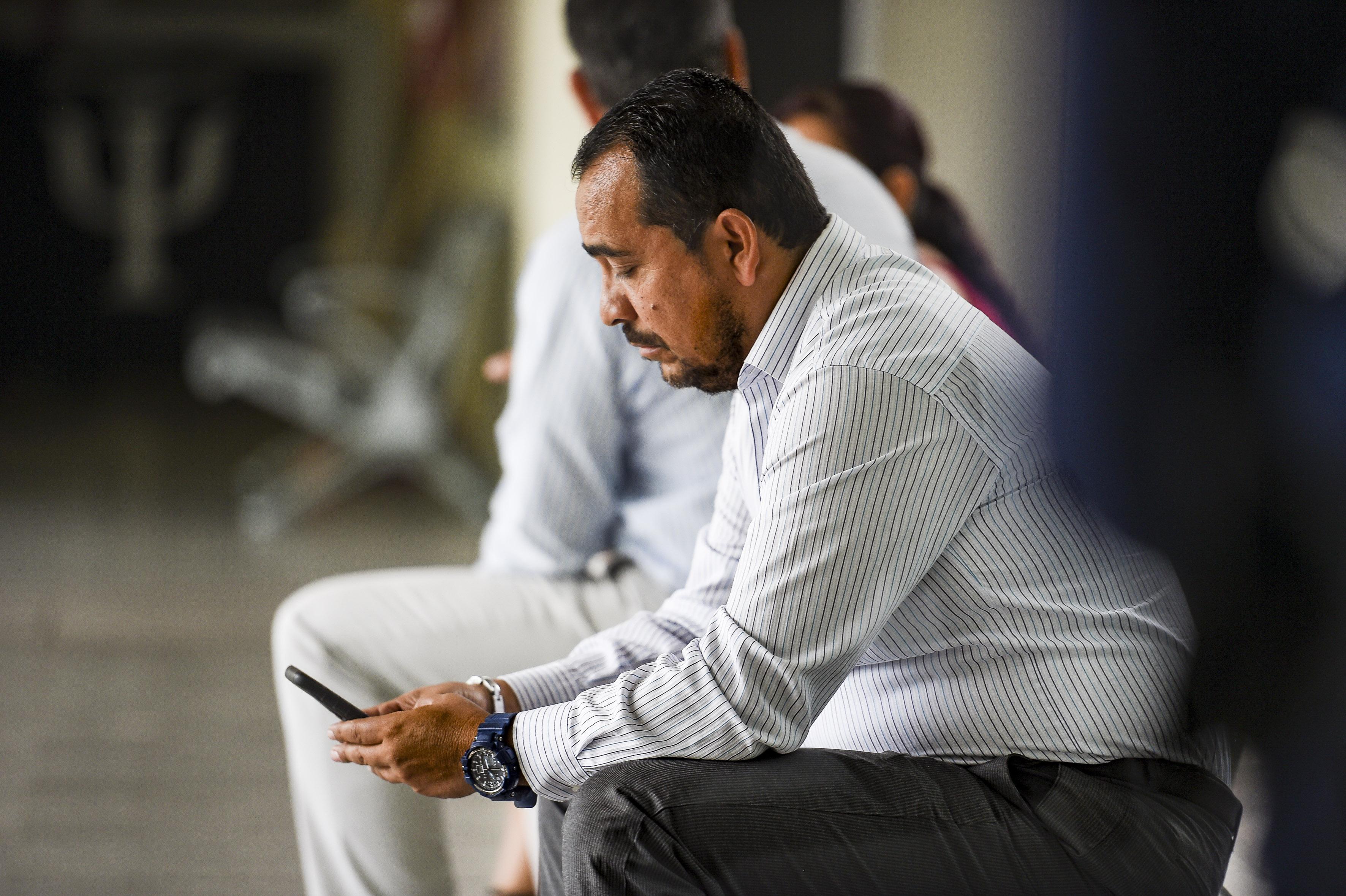 Persona sentada usando su celular