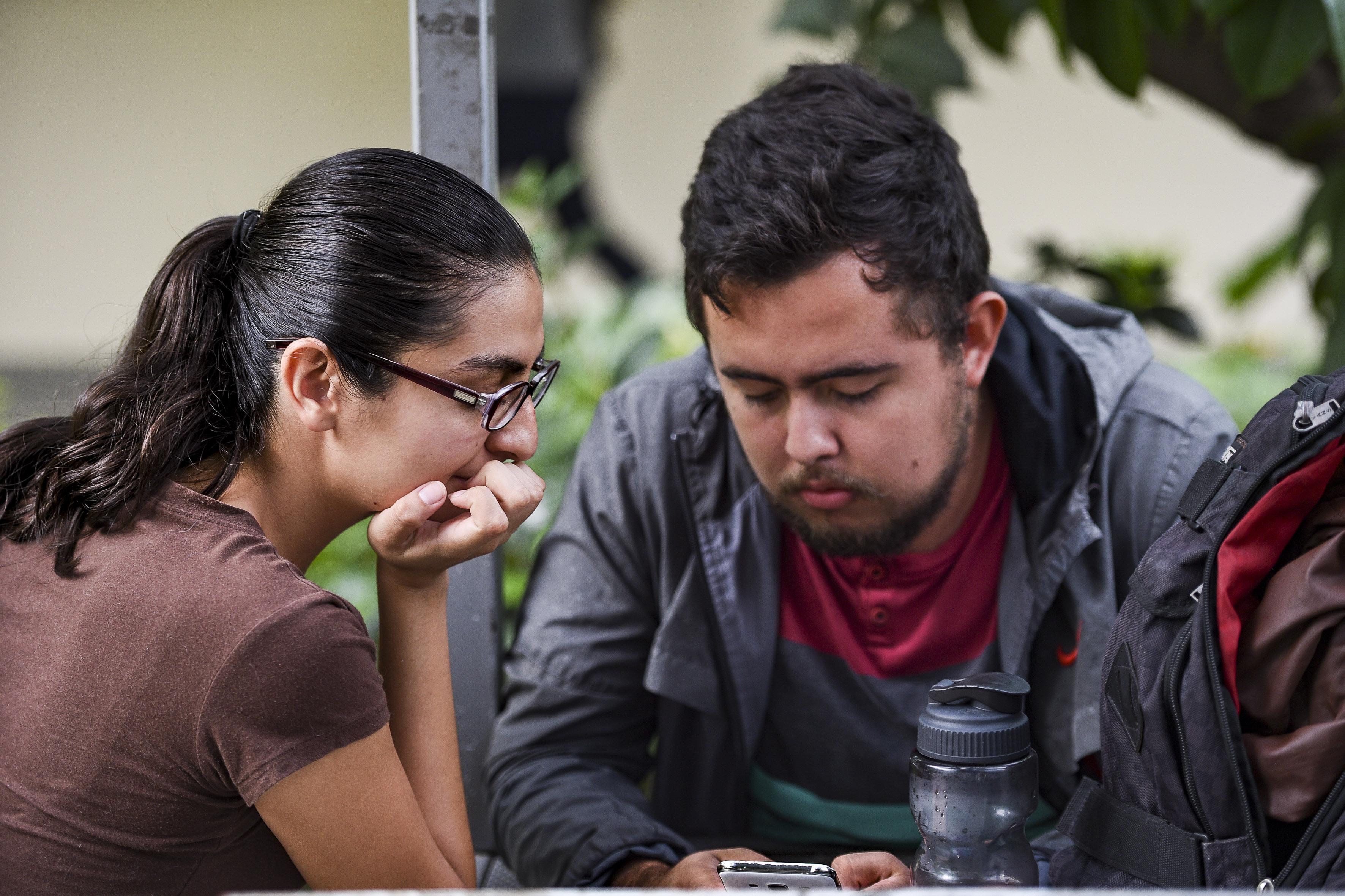 Alumno del CUCS le muestra a compañera contenido de su celular