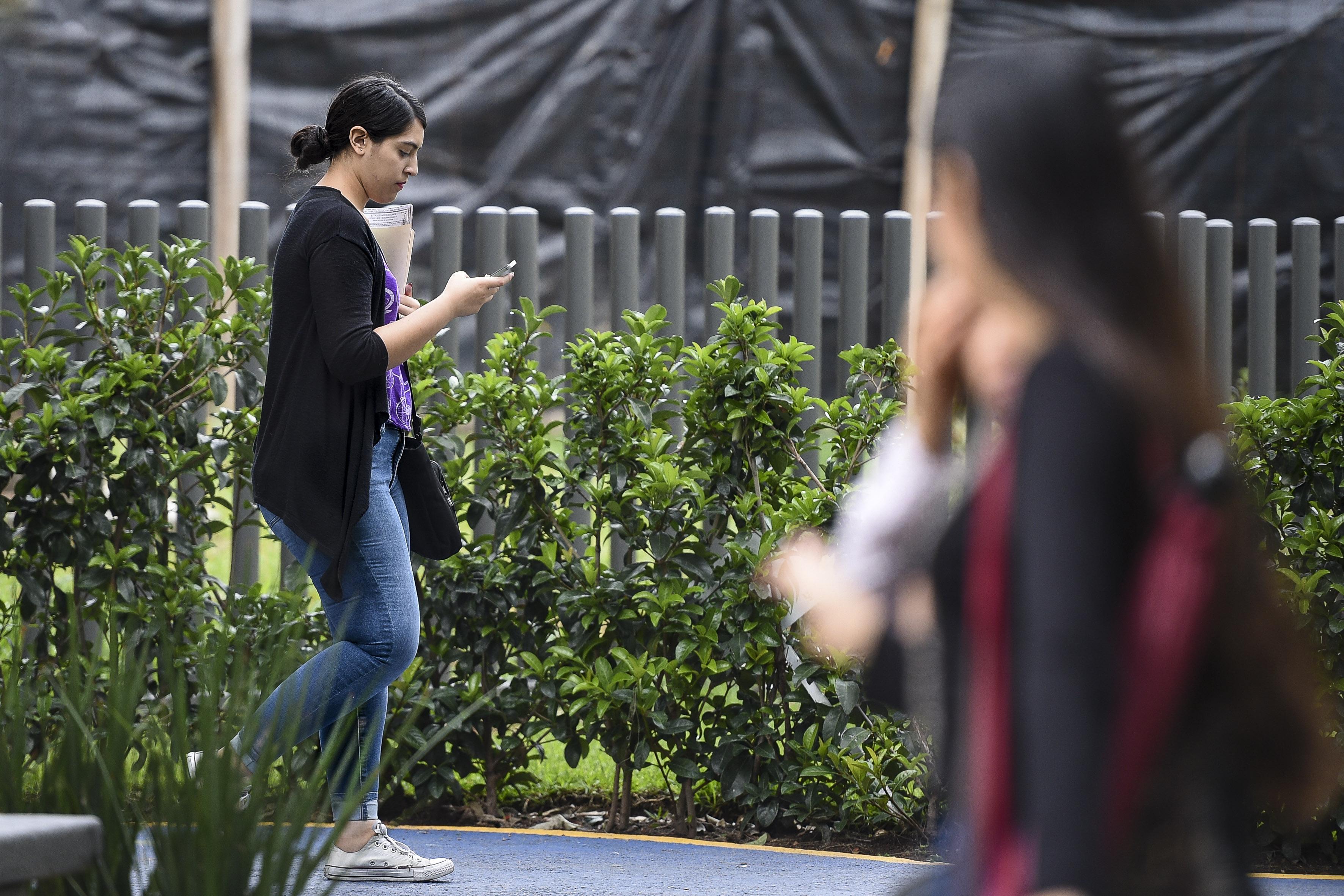 Alumna del CUCS va caminando y a su vez texteando en su celular