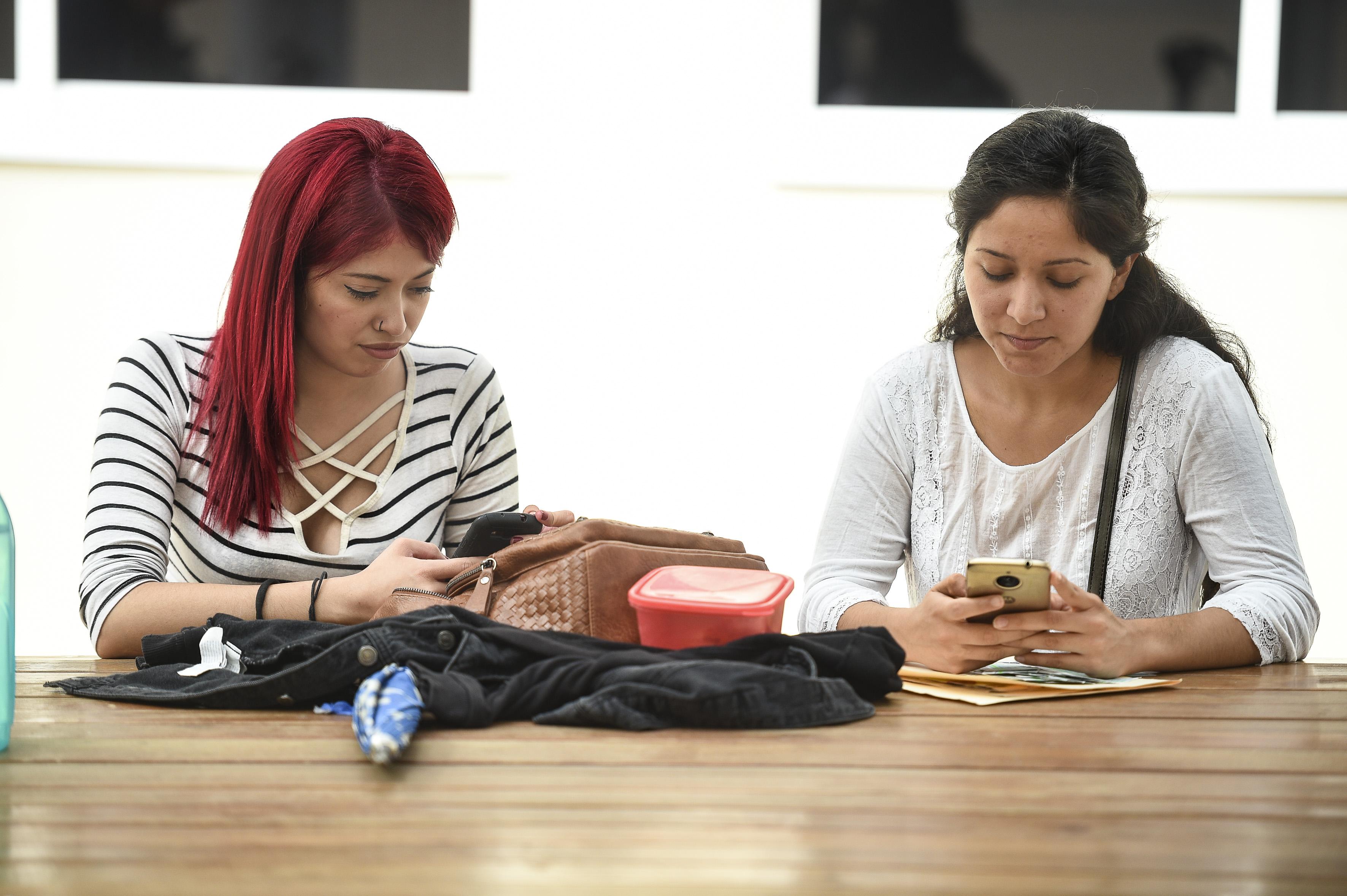Alumnas del CUCS sentadas juntas usando el celular