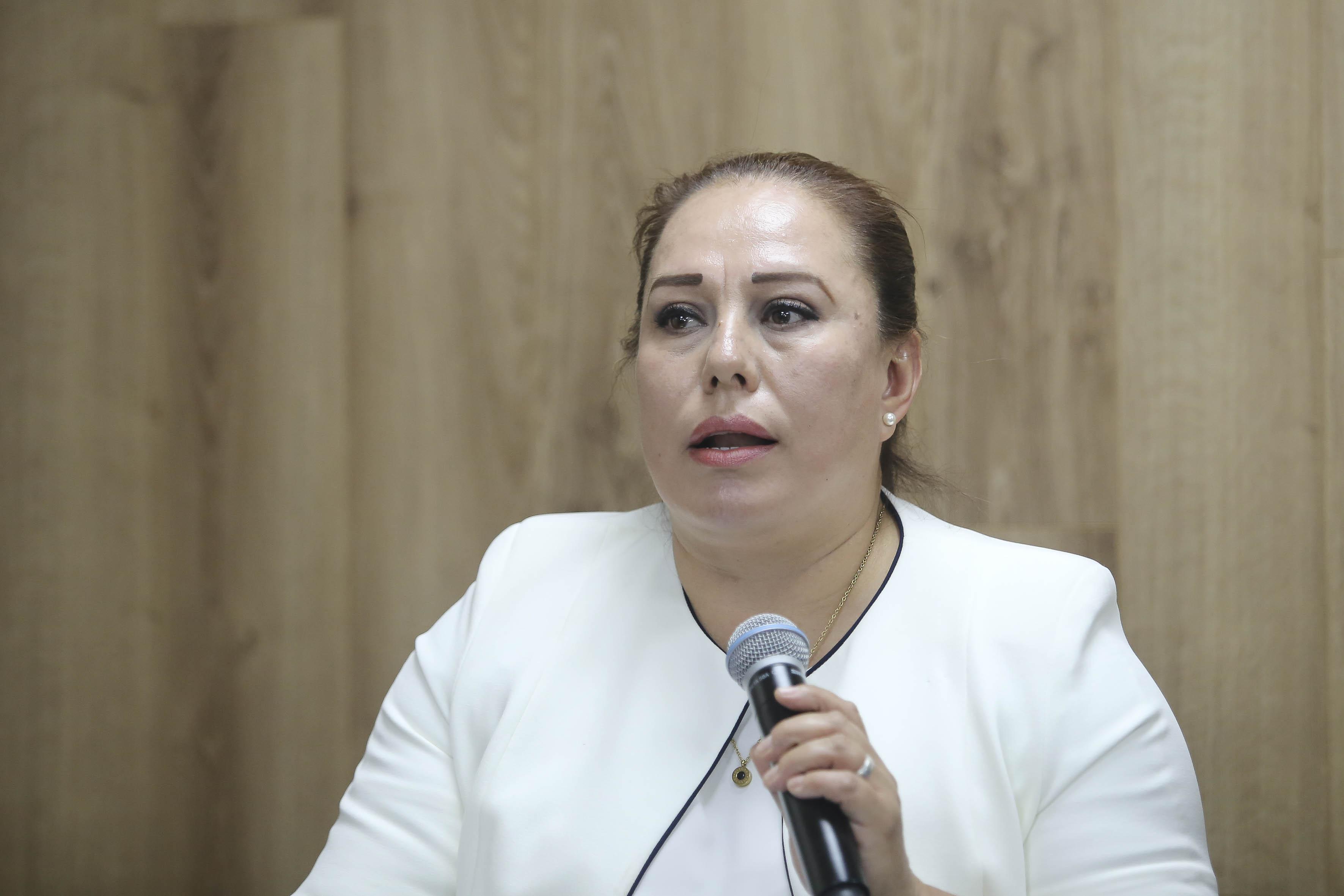 Mtra. Isabel Gómez al micrófono en rueda de prensa
